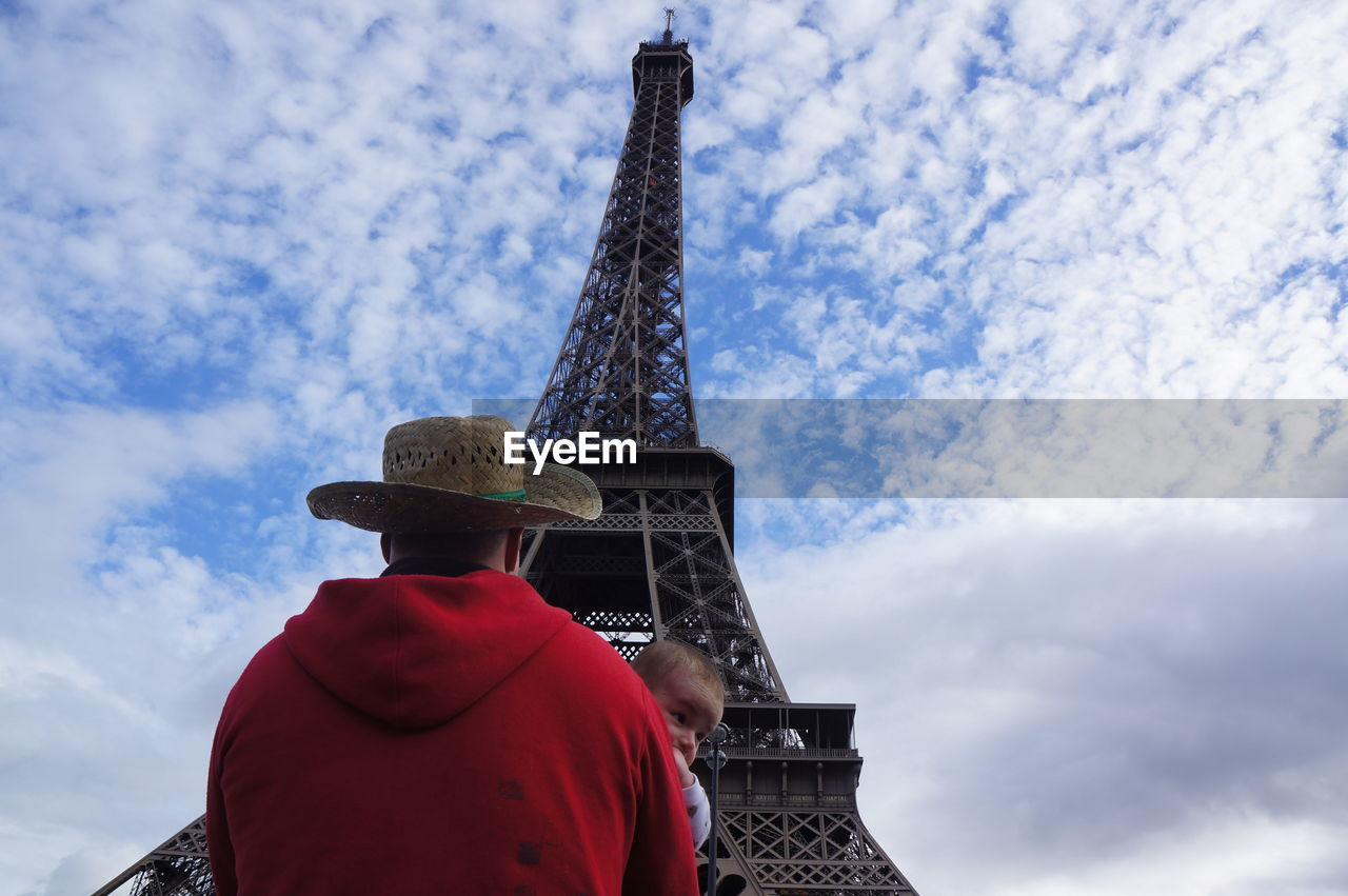 Low angle view of father carrying baby by eiffel tower against cloudy sky