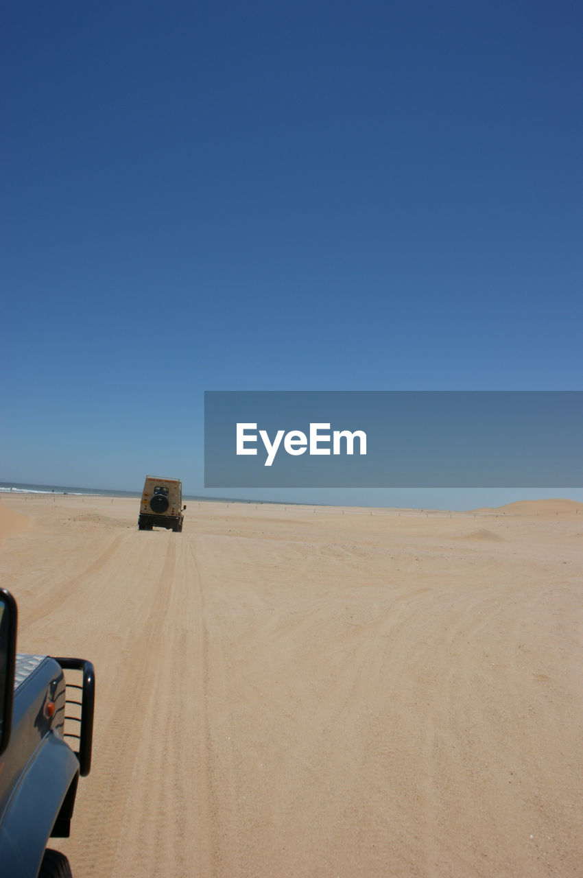 copy space, clear sky, nature, sand, desert, landscape, transportation, blue, arid climate, scenics, day, mode of transport, no people, outdoors, sand dune, off-road vehicle, beauty in nature, land vehicle, sky