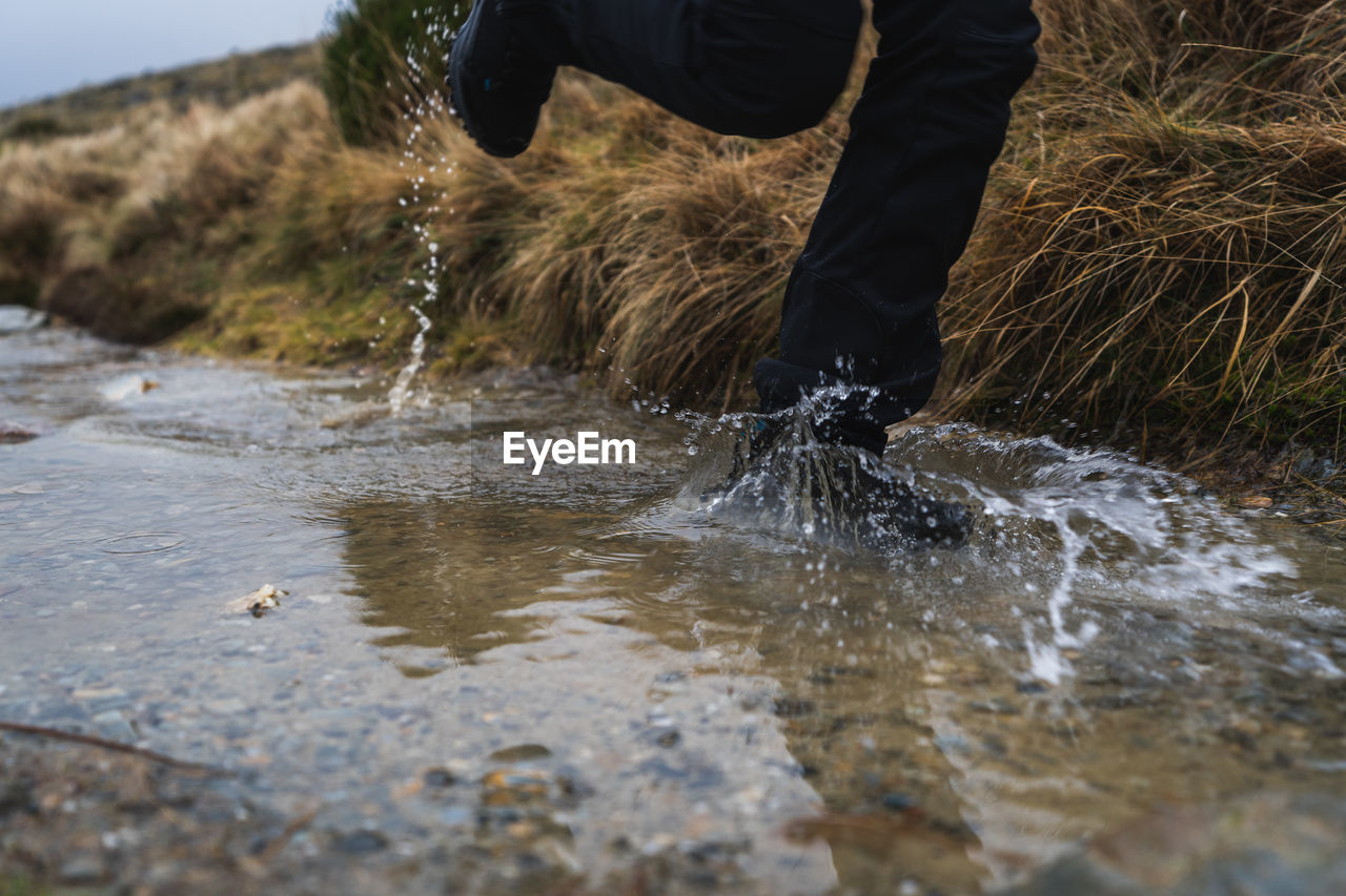 Low section of person running in puddle