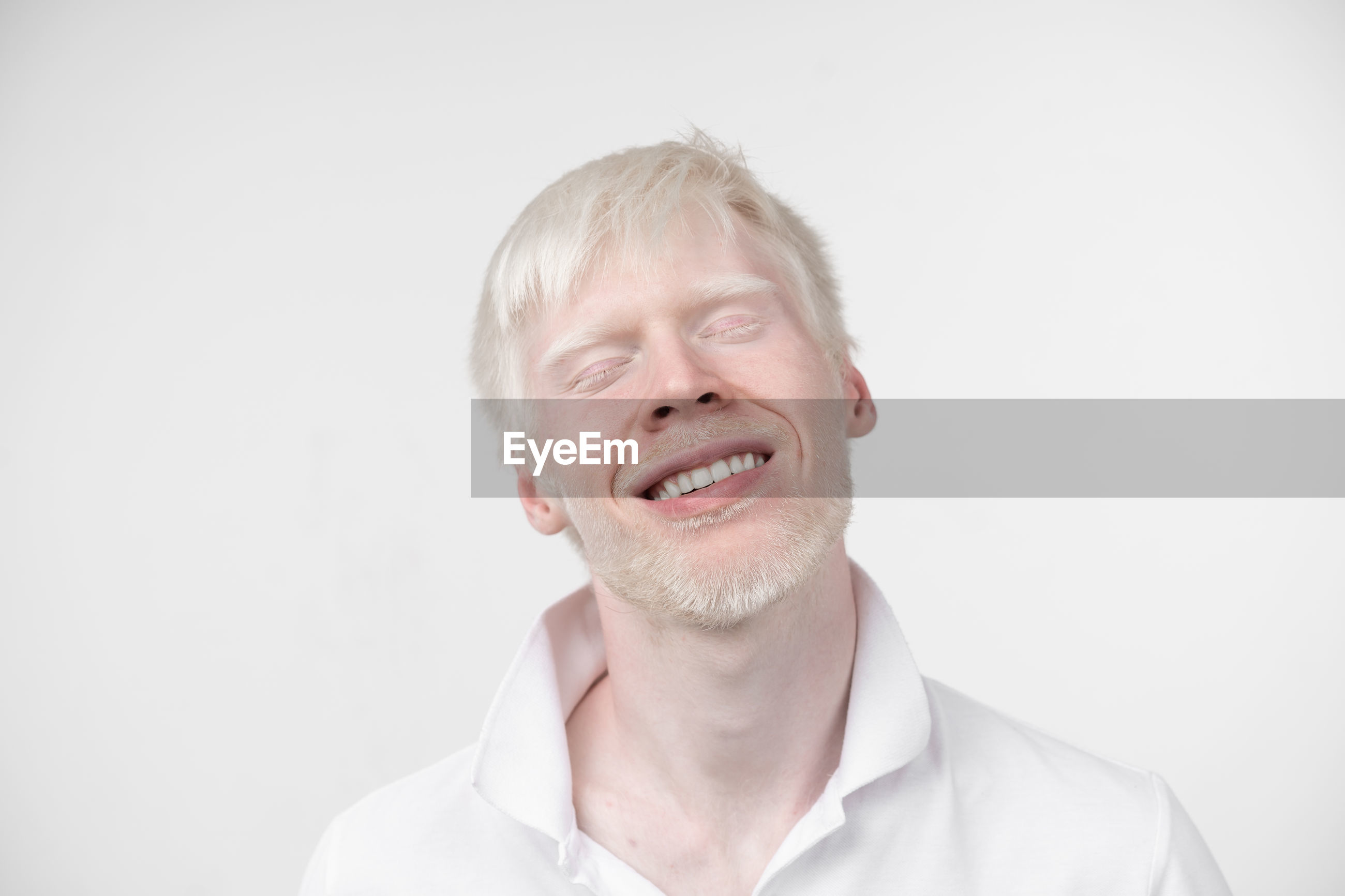 Close-up of smiling man with eyes closed standing against white background