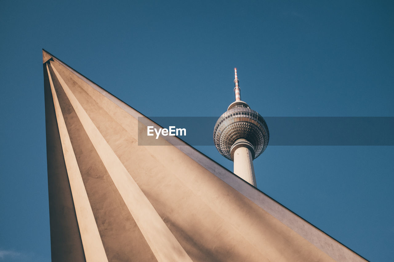 Low angle view of fernsehturm against clear blue sky