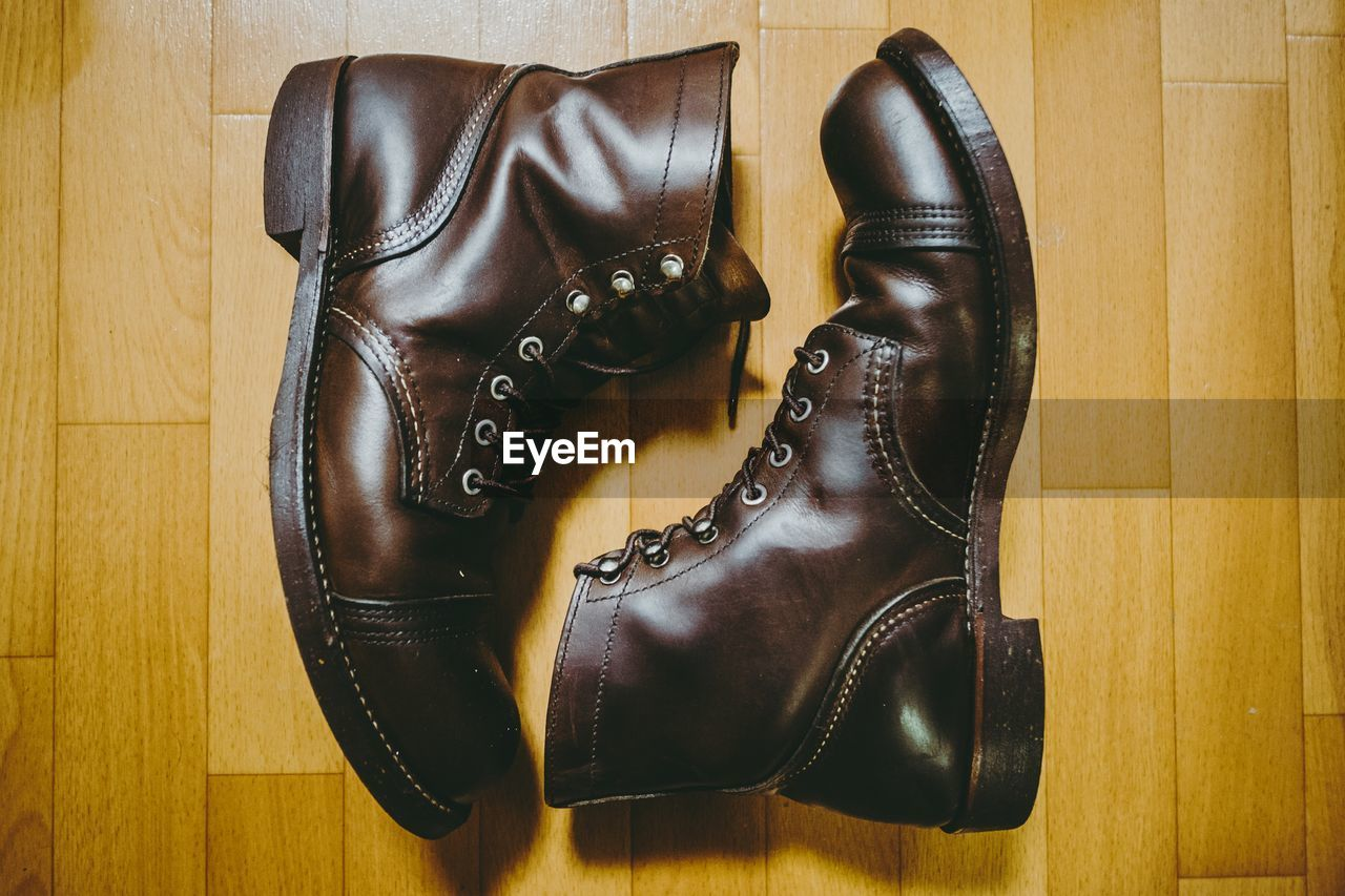 shoe, leather, indoors, no people, black color, pair, wood, still life, boot, flooring, hardwood floor, wood - material, brown, close-up, high angle view, fashion, shoelace, table, two objects, home interior, personal accessory, compatibility, menswear