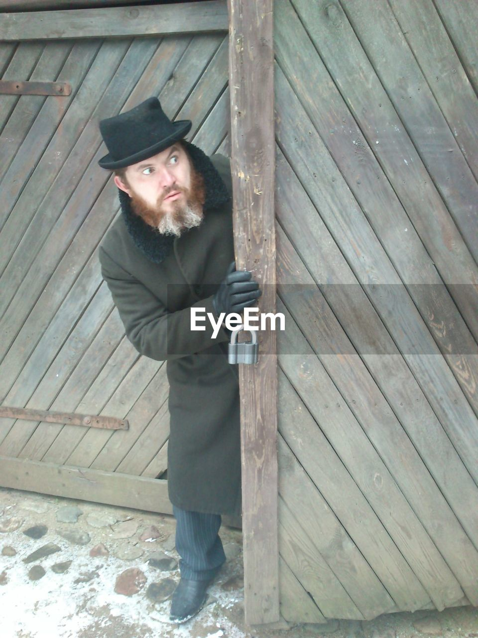 Full length of bearded man looking away while standing by wooden door