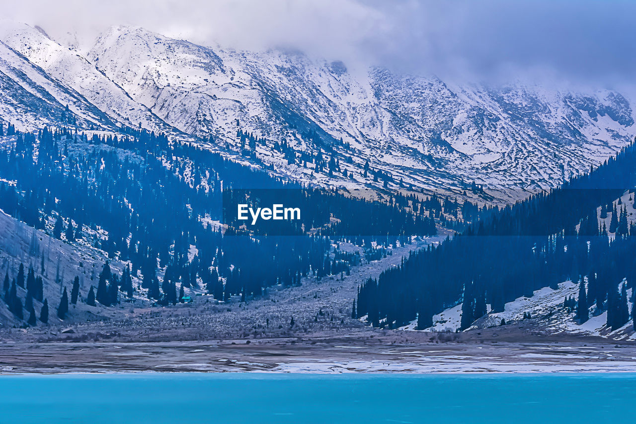 cold temperature, snow, winter, mountain, beauty in nature, nature, weather, scenics, mountain range, snowcapped mountain, tranquil scene, tranquility, frozen, landscape, outdoors, tree, ice, no people, cloud - sky, pine tree, day, sky, lake, travel destinations, water, wilderness area