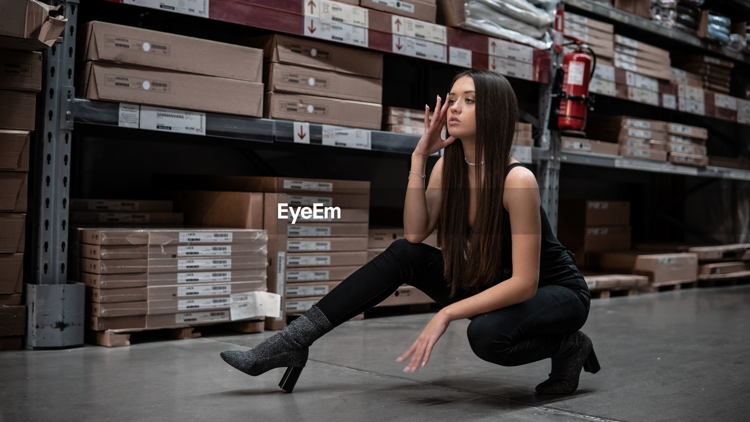 Full length of young woman stretching on floor in warehouse