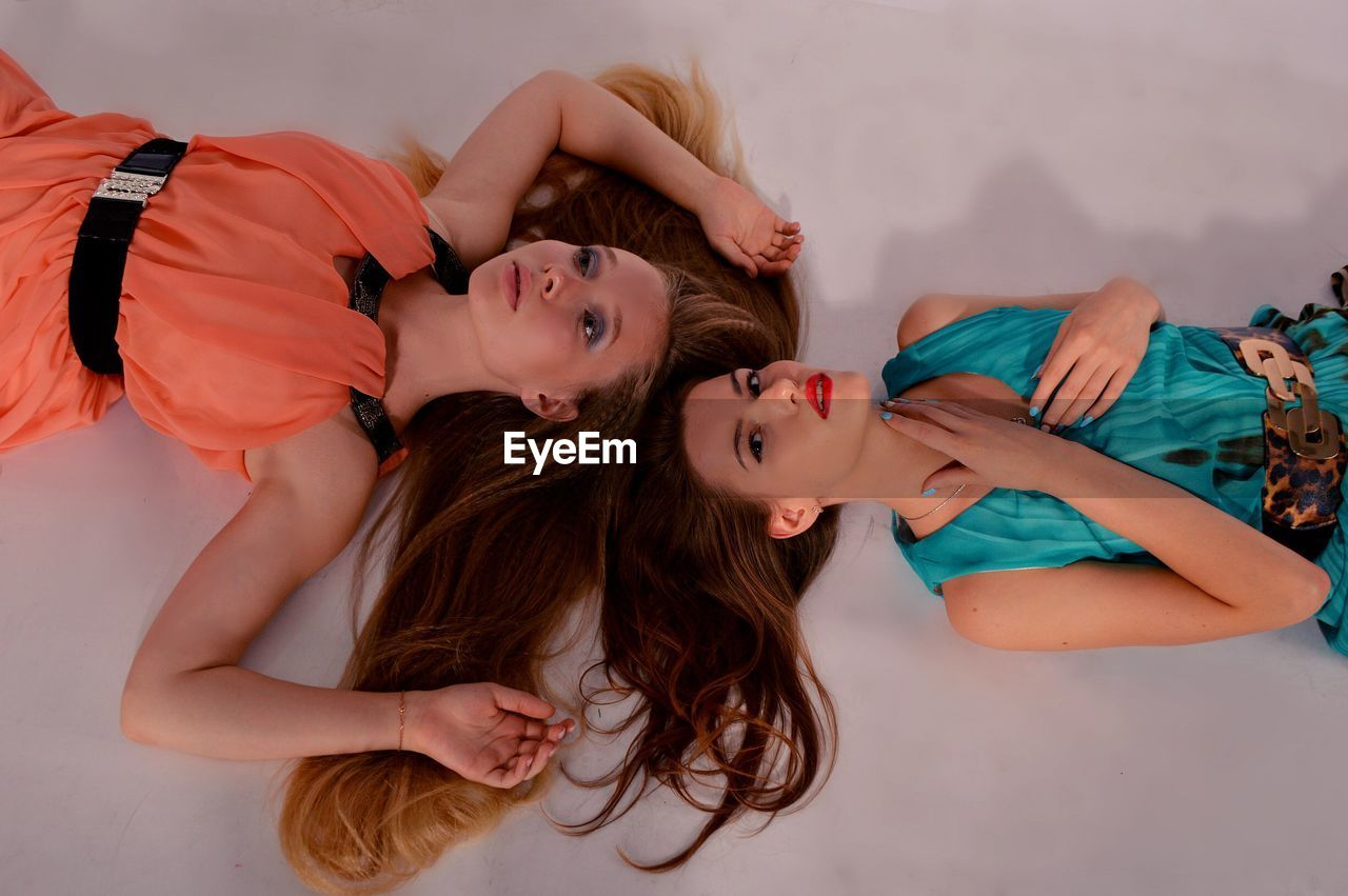 High angle view of female models lying on floor