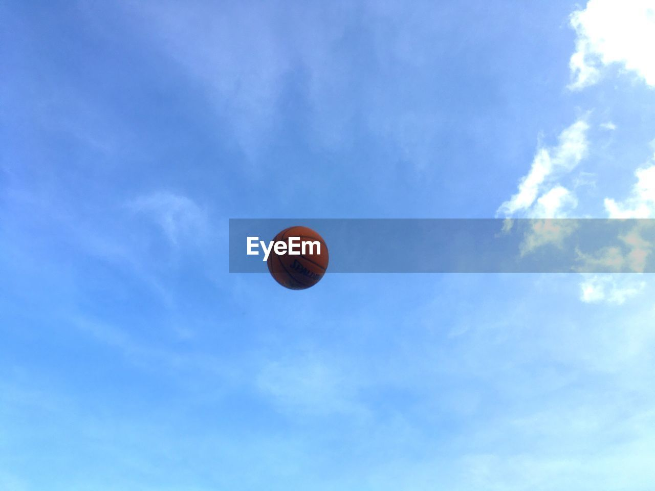 sky, low angle view, basketball - sport, cloud - sky, blue, mid-air, ball, day, no people, sport, nature, outdoors, beauty in nature