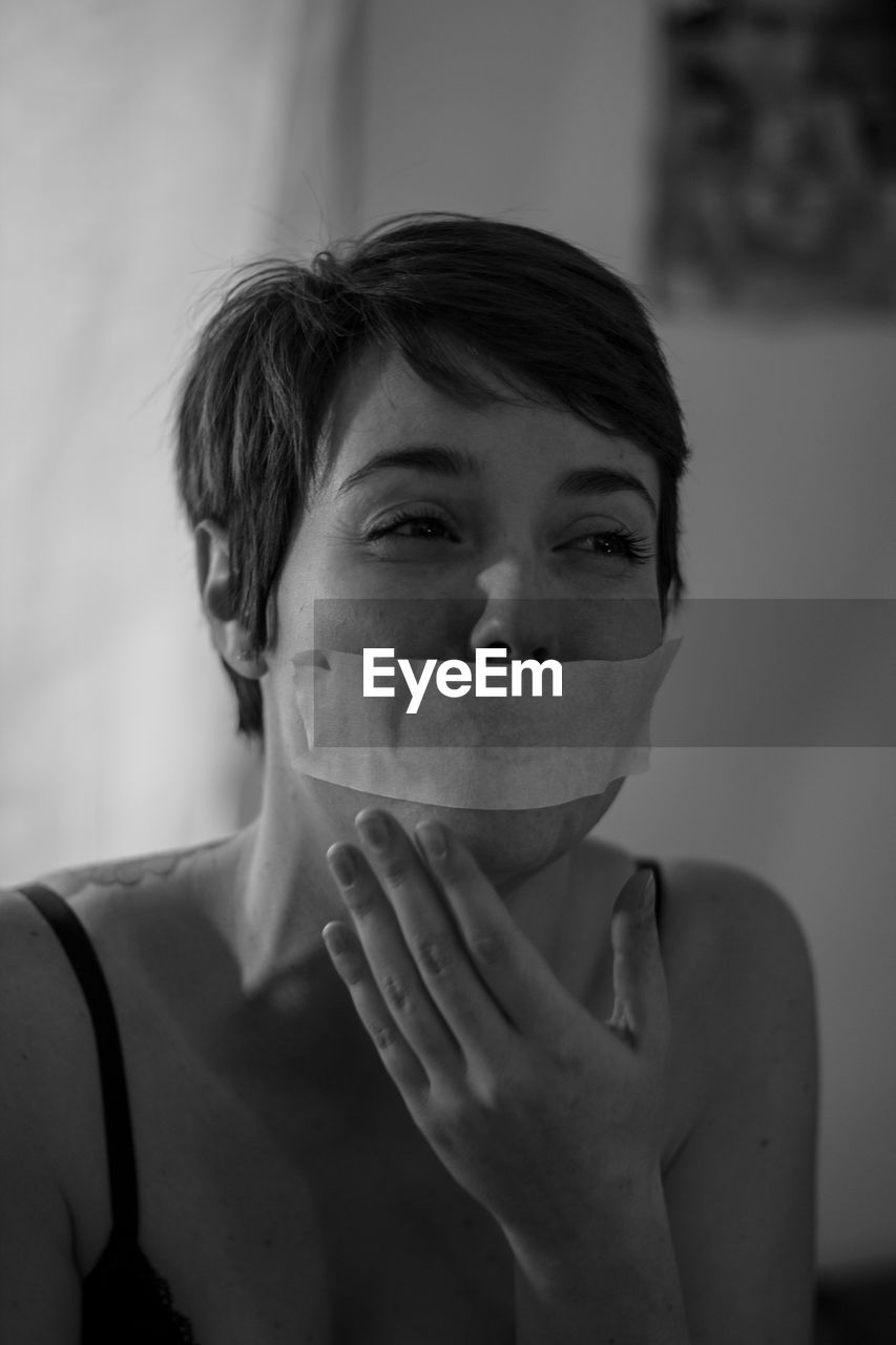 Crying woman with duct tape on mouth