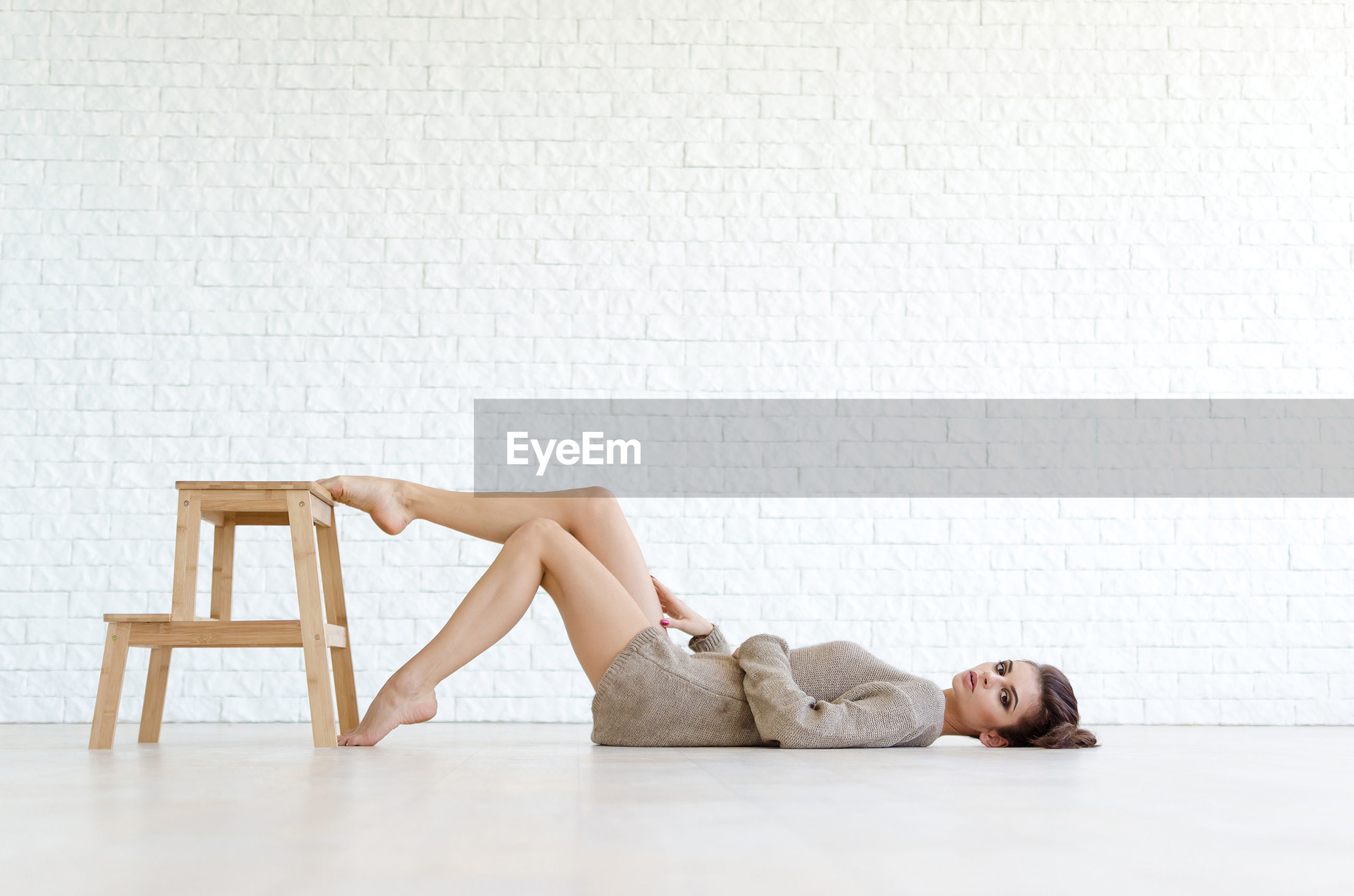 SIDE VIEW OF WOMAN RESTING ON SEAT AGAINST TILED FLOOR