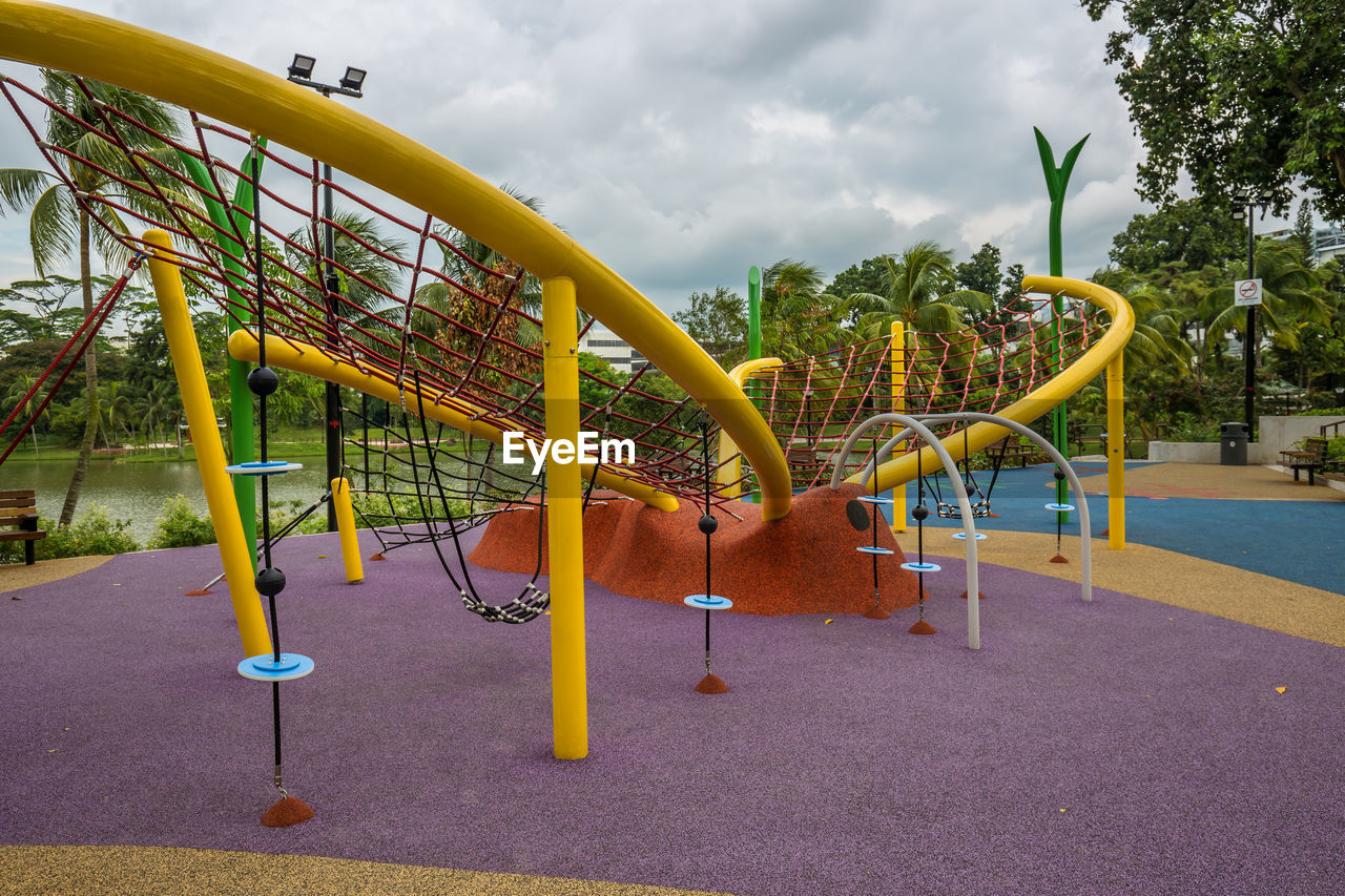 playground, childhood, park, plant, absence, tree, cloud - sky, day, park - man made space, sky, outdoor play equipment, nature, empty, outdoors, yellow, multi colored, metal, swing, slide, jungle gym