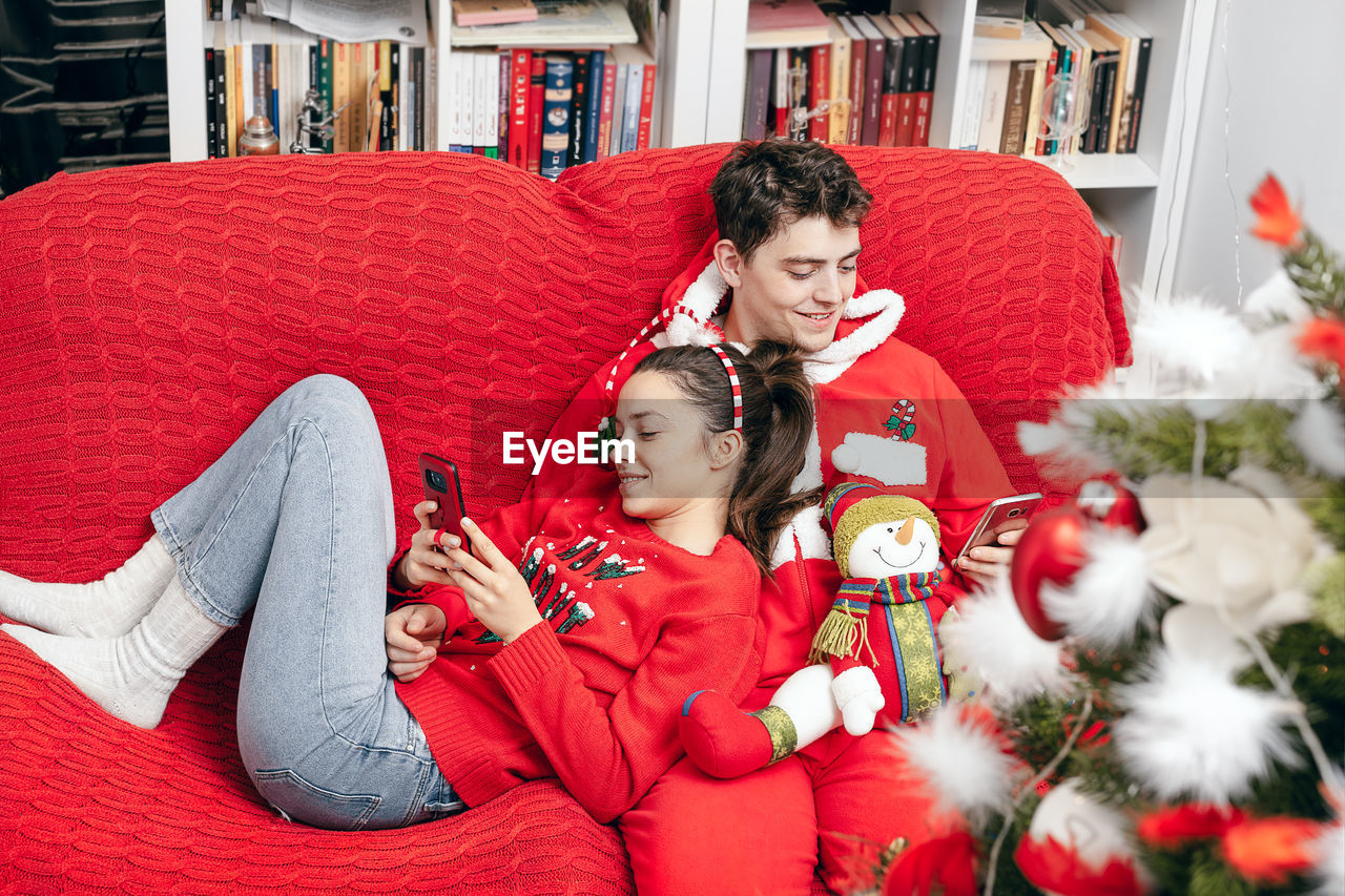 Young Couple Sitting On Red Sofa During Christmas At Home