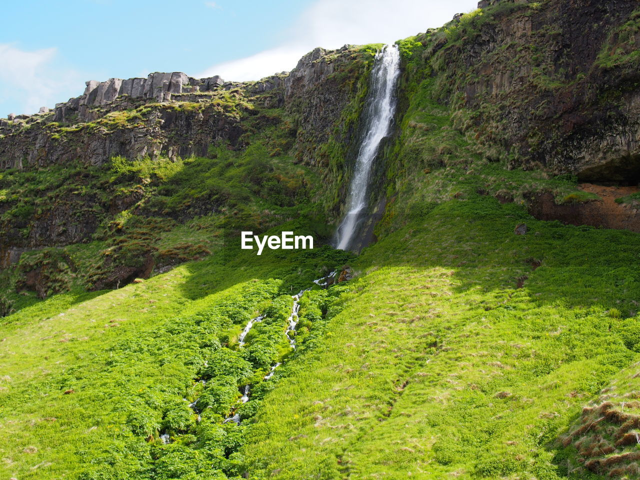 scenics - nature, beauty in nature, plant, land, nature, waterfall, environment, green color, motion, water, no people, day, sky, mountain, grass, growth, flowing water, landscape, tree, outdoors, flowing, formation