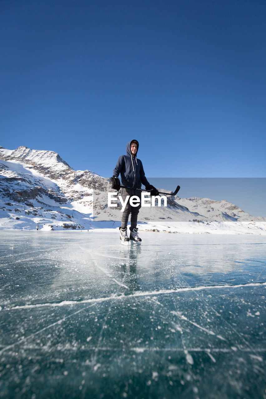 Young Man Playing Ice Hockey On Frozen Lake By Snowcapped Mountain Against Clear Sky
