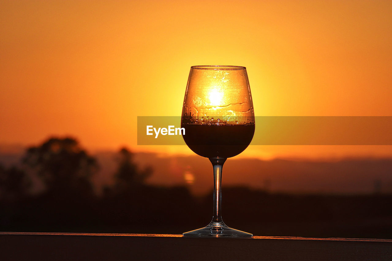 sunset, orange color, focus on foreground, drink, sun, refreshment, no people, close-up, sky, beauty in nature, nature, wineglass, outdoors, scenics, alcohol, yellow, freshness, clear sky, day