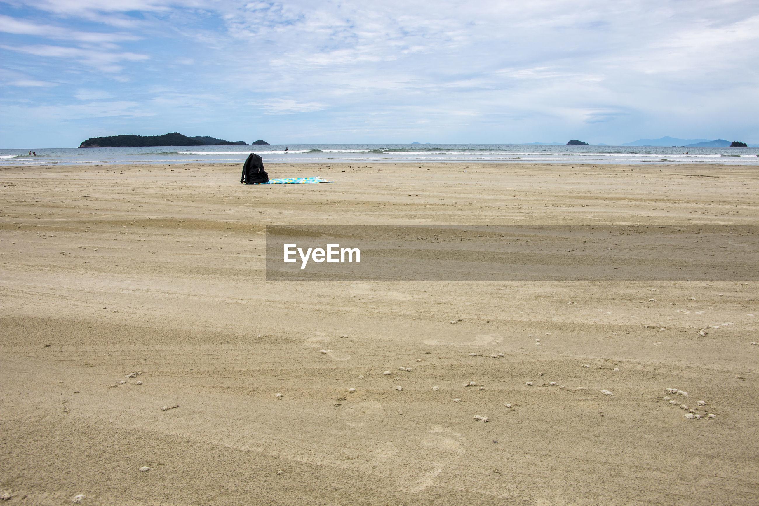Abandoned bag on sand at beach against sky