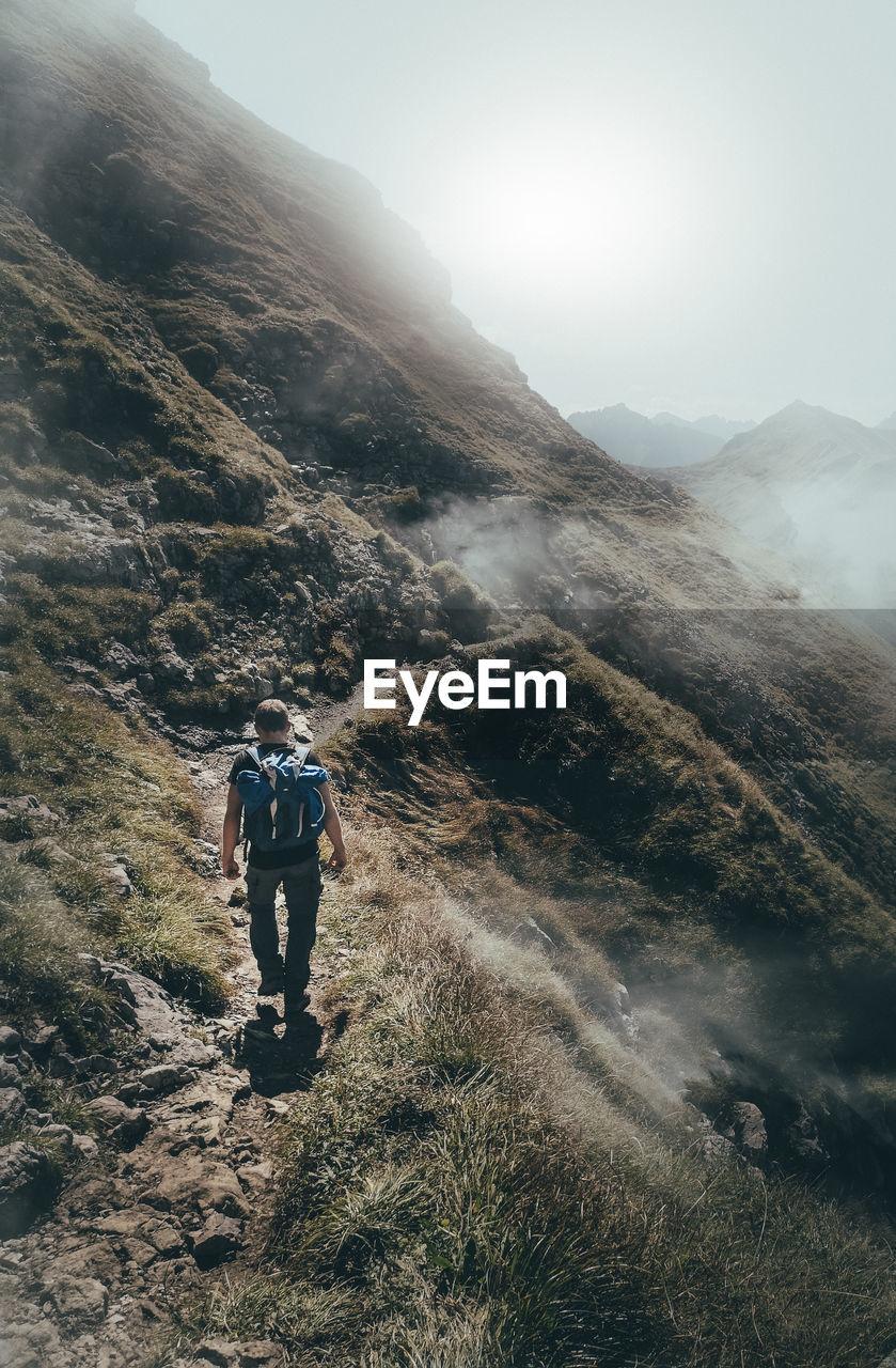 Rear view of backpacker walking on mountain