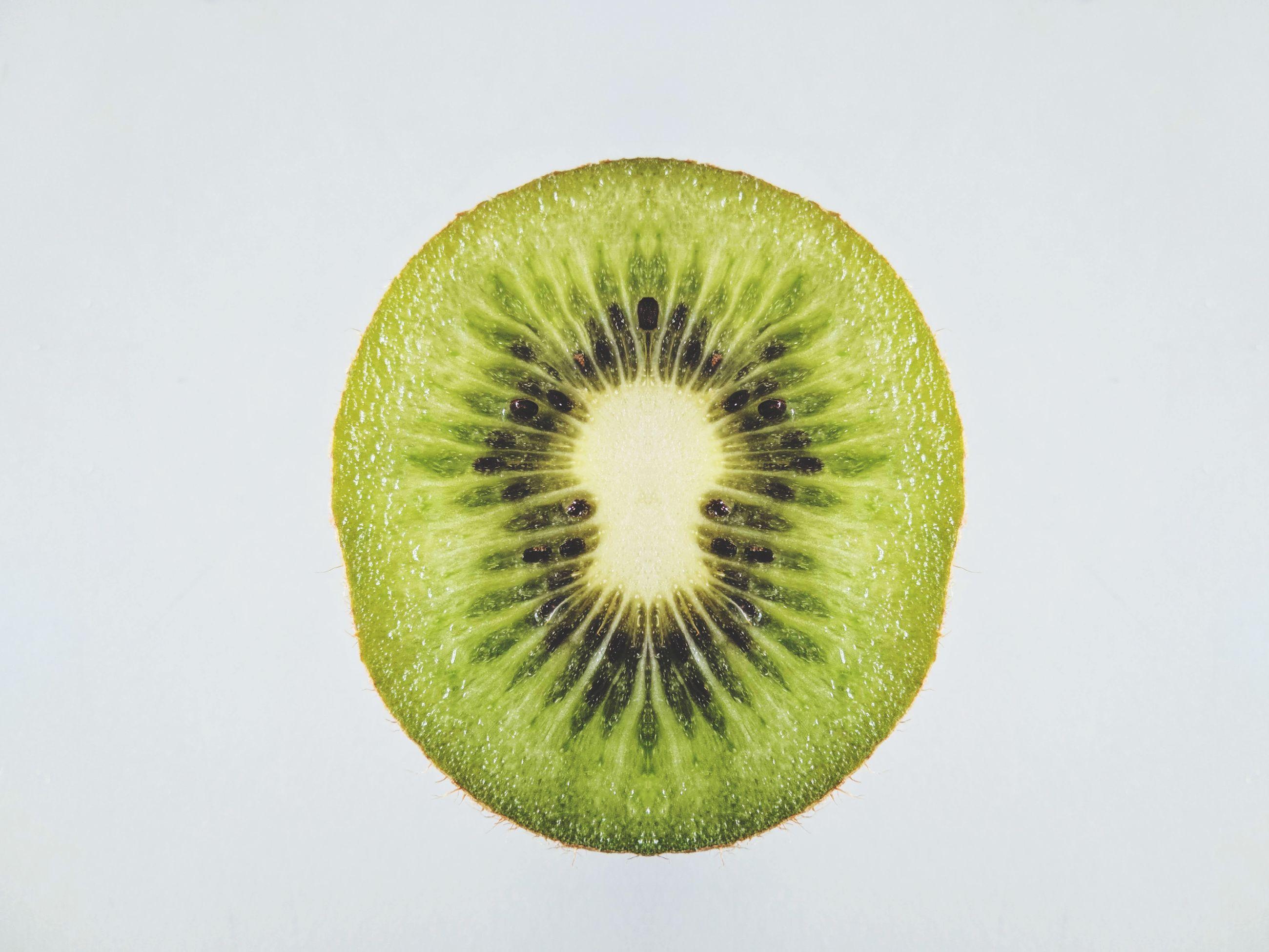 Close-up of kiwi against white background