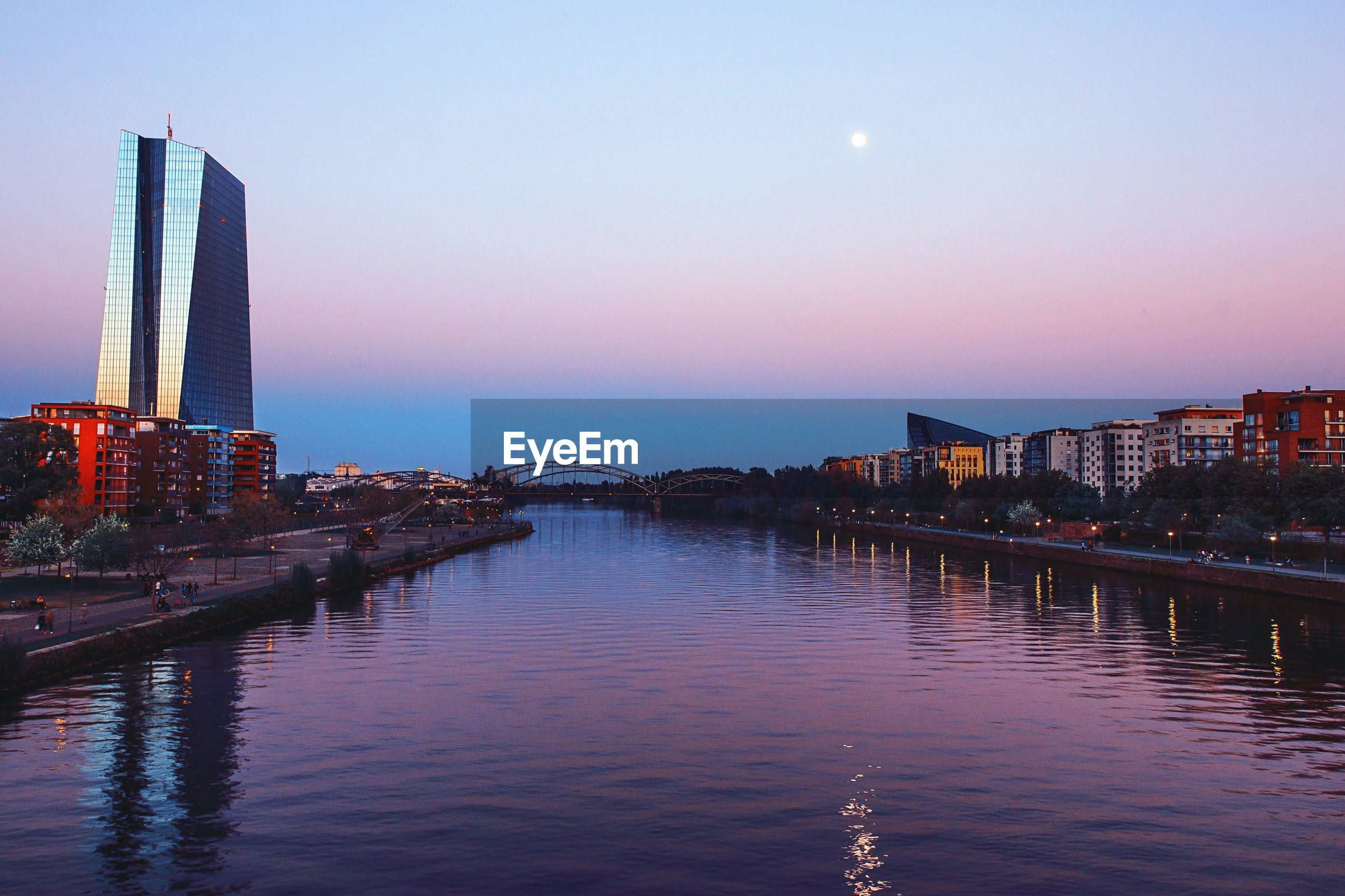 RIVER BY ILLUMINATED CITY AGAINST CLEAR SKY AT NIGHT