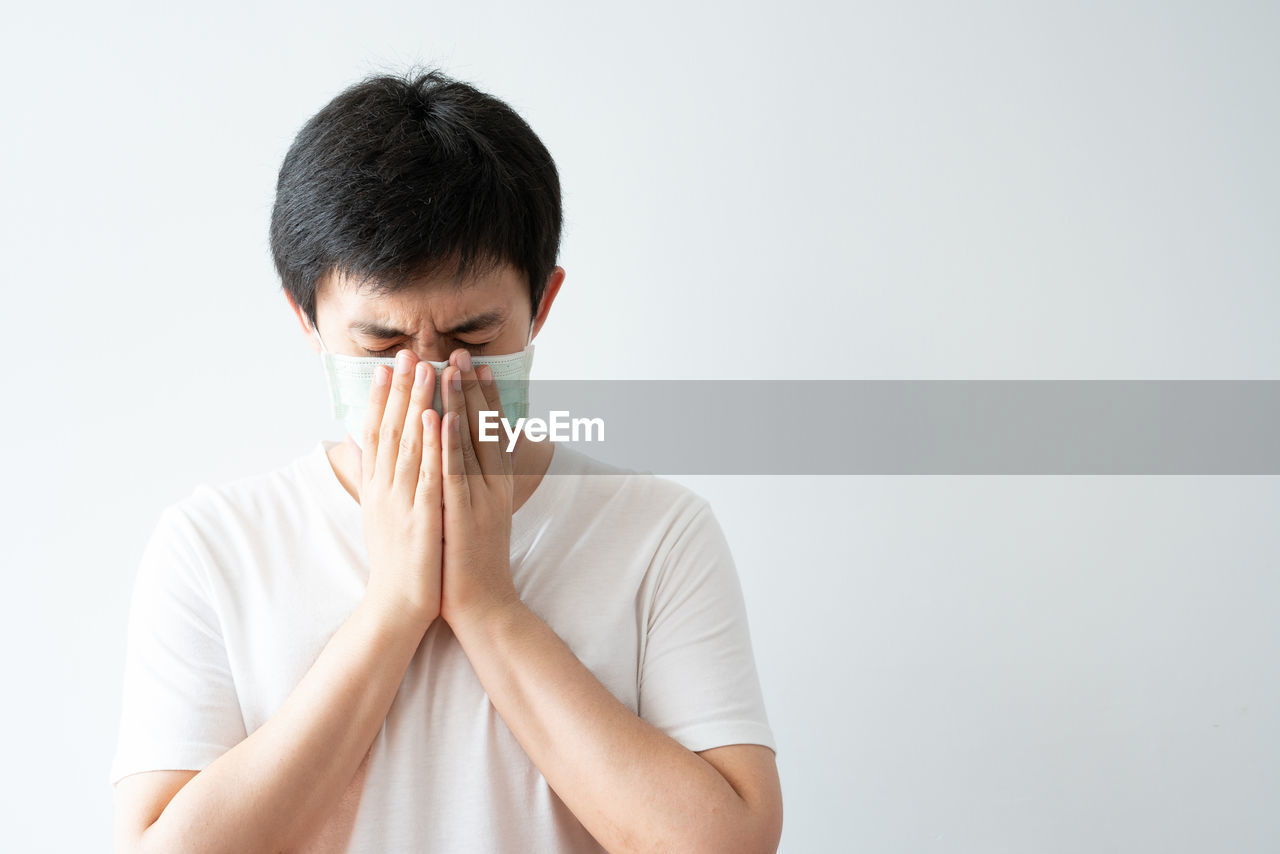 PORTRAIT OF A YOUNG MAN COVERING FACE AGAINST WHITE BACKGROUND