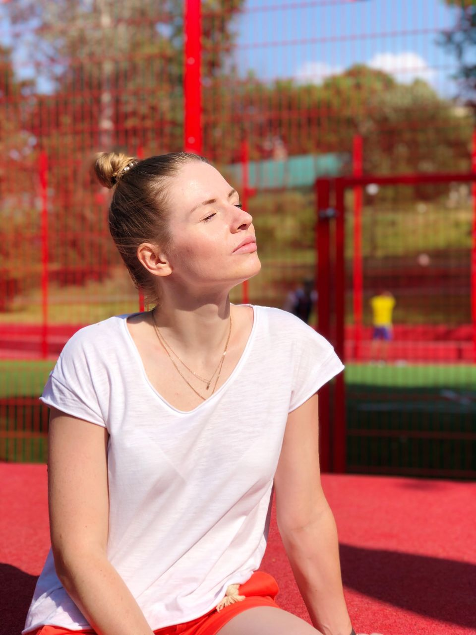 Woman with eyes closed sitting against red fence during sunny day
