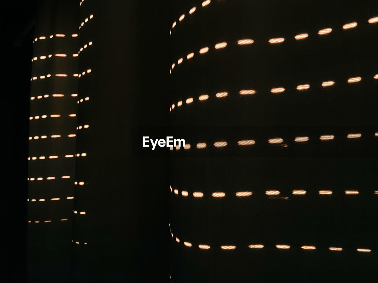 Full frame shot of illuminated light bulbs in building