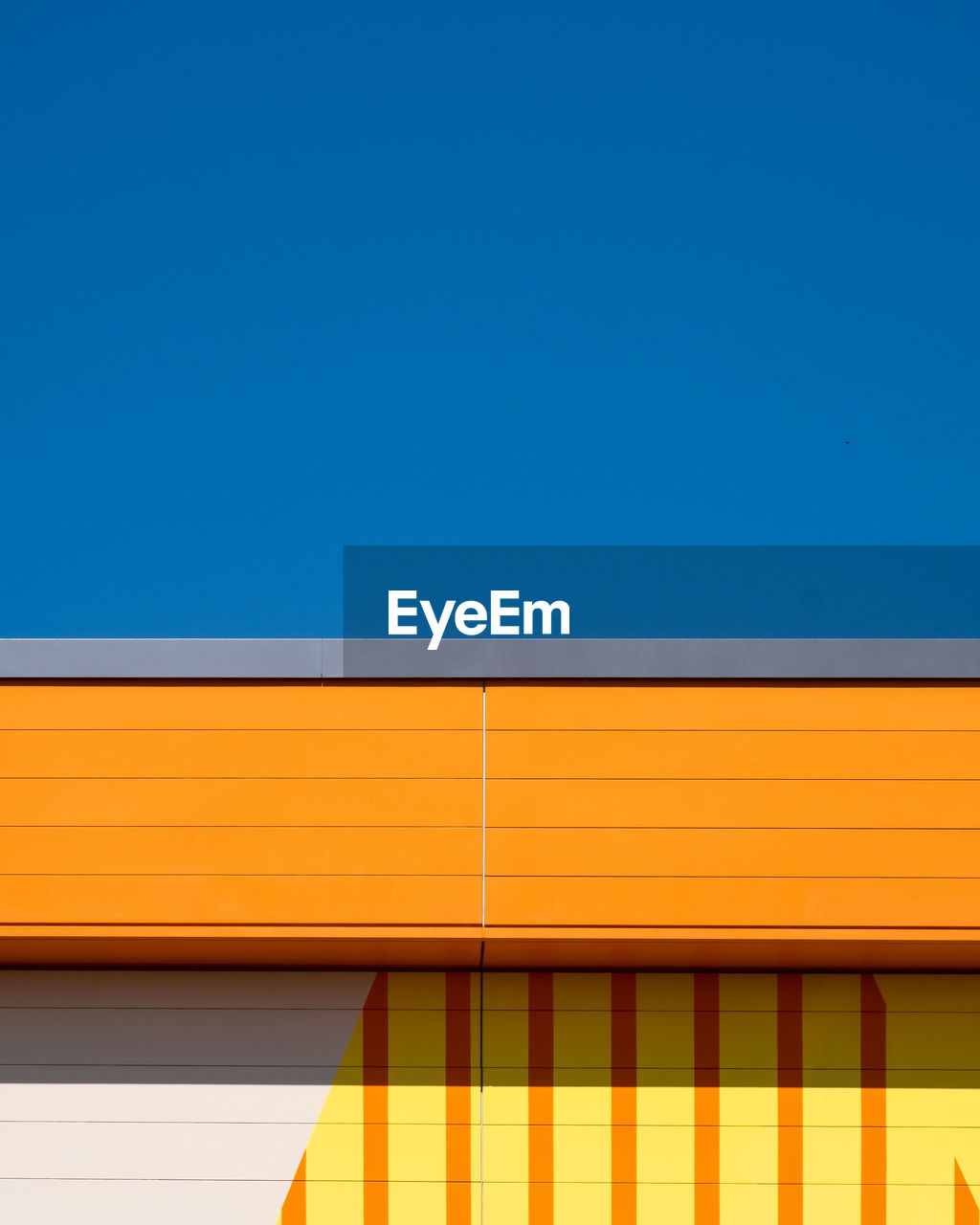 copy space, architecture, blue, built structure, clear sky, yellow, no people, multi colored, building exterior, wall - building feature, low angle view, sky, day, pattern, public transportation, outdoors, close-up, striped, orange color, building