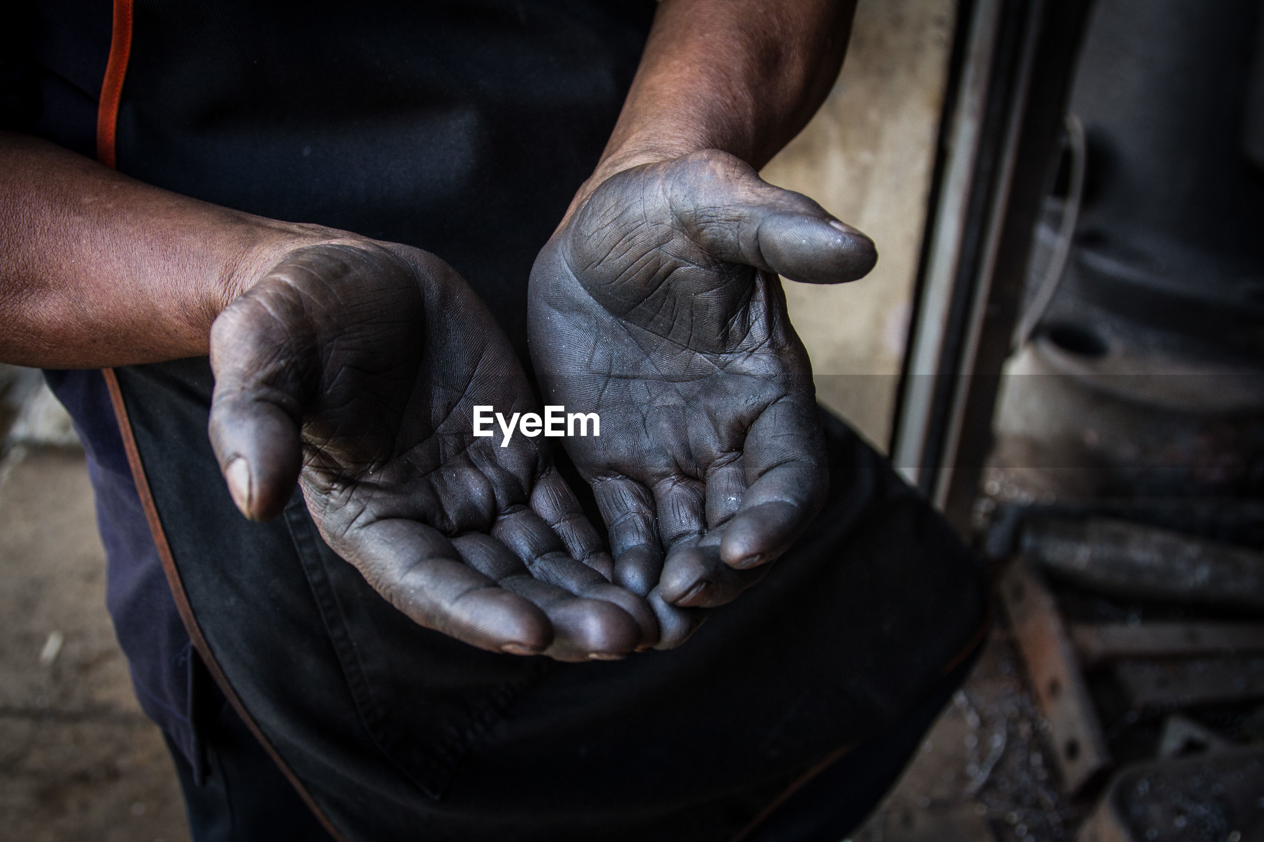 Midsection of manual worker showing dirty hands in factory