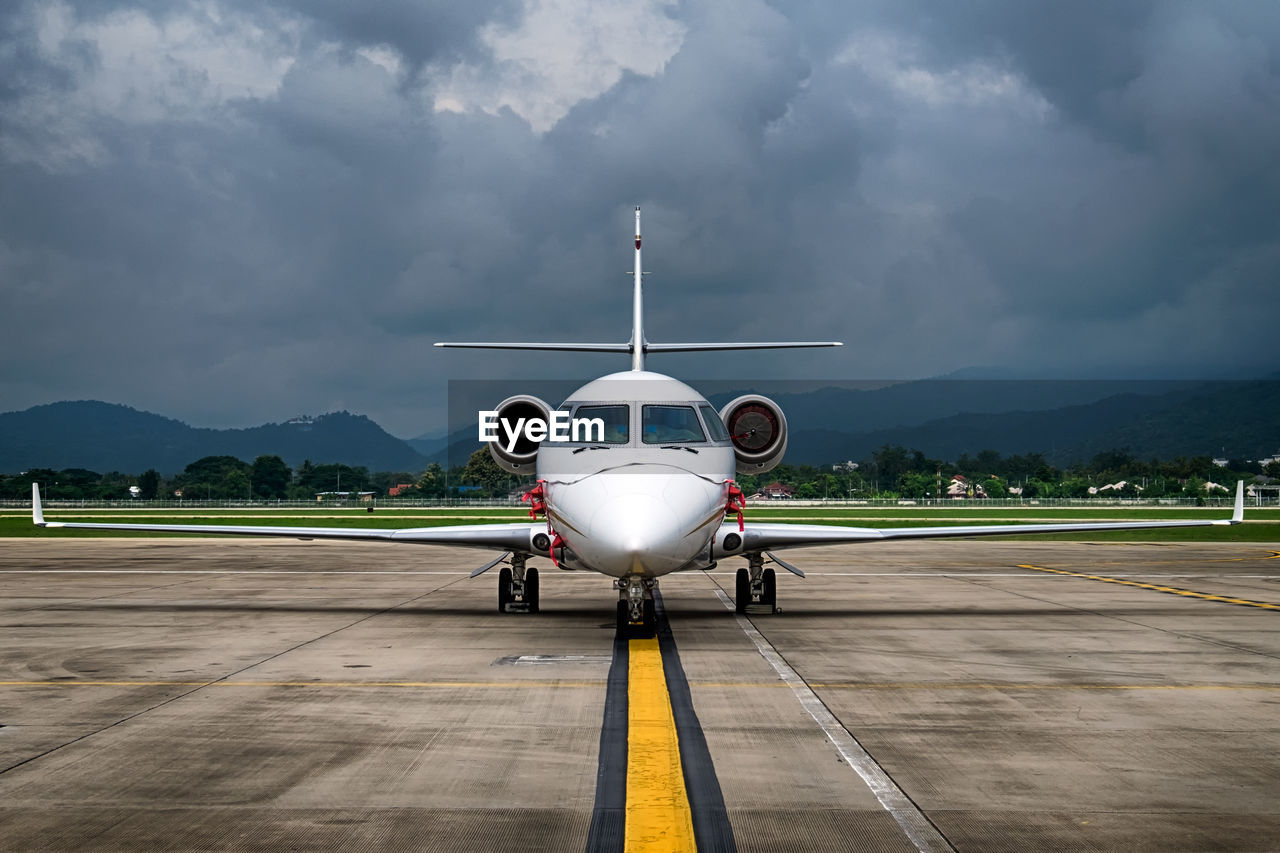 airplane, airport runway, cloud - sky, transportation, airport, air vehicle, mode of transport, sky, mountain, runway, stationary, day, outdoors, mountain range, storm cloud, no people, commercial airplane, technology, nature
