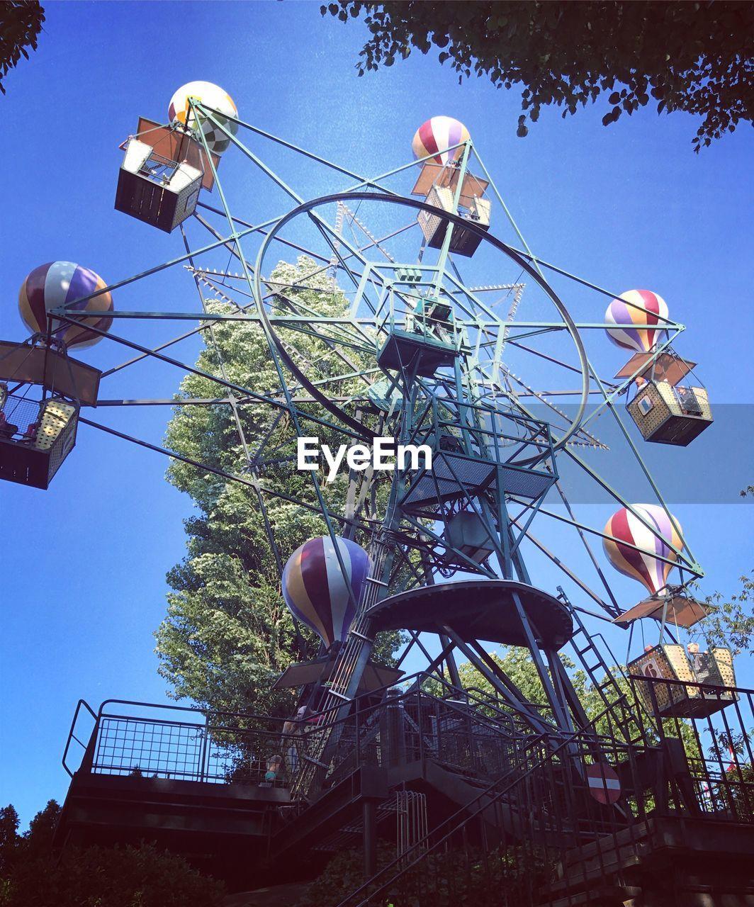amusement park, low angle view, amusement park ride, arts culture and entertainment, day, sky, outdoors, built structure, clear sky, blue, ferris wheel, tree, no people, architecture