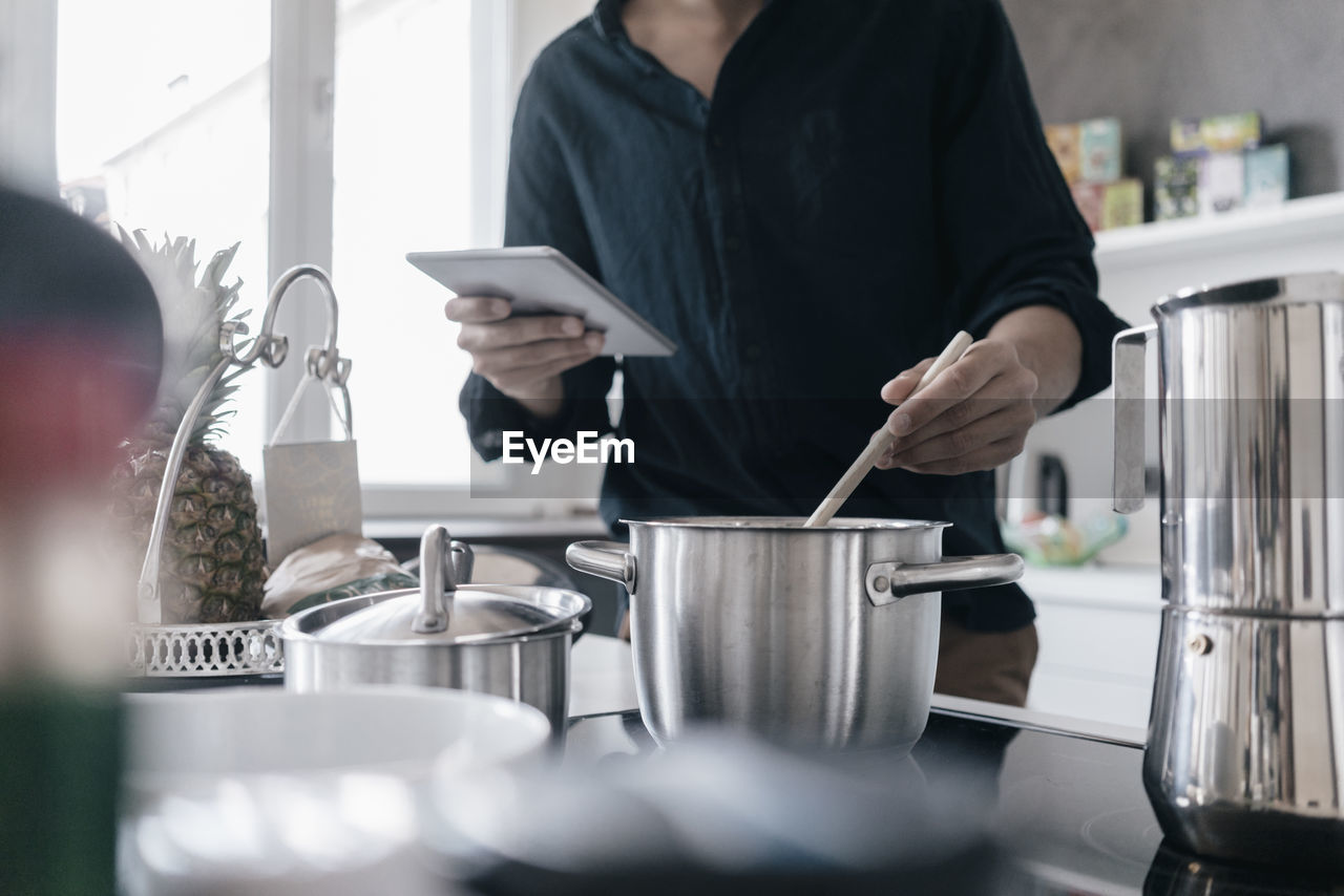 MAN USING MOBILE PHONE IN KITCHEN