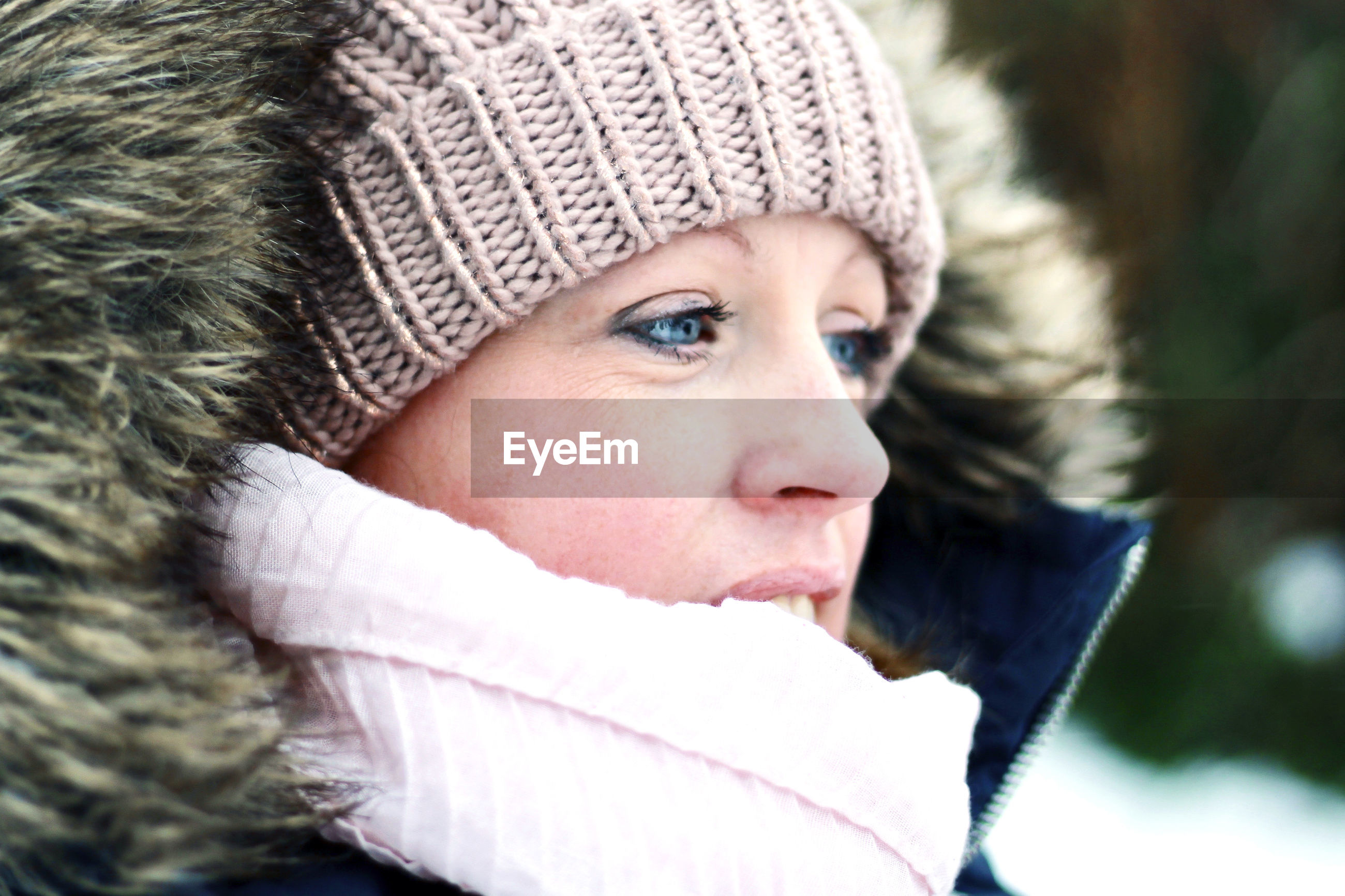 Close-up of woman in warm clothing looking away