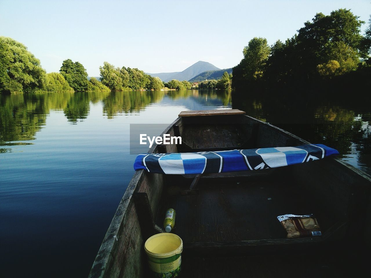 Wooden boat on lake by trees and mountains against clear sky