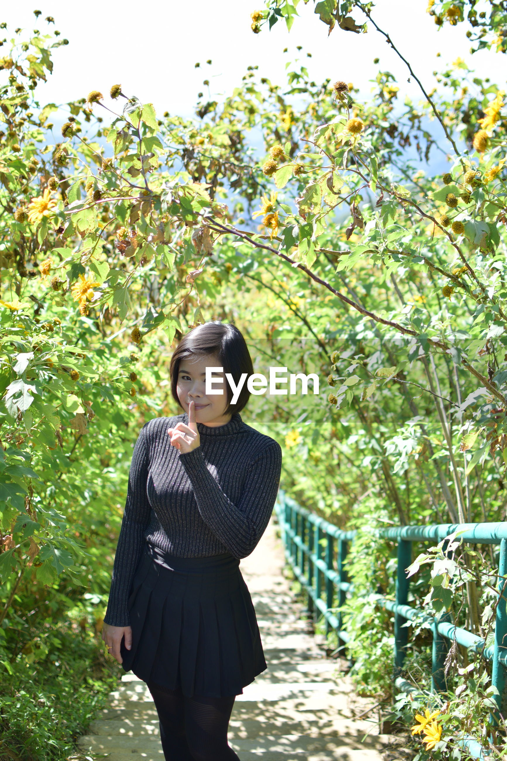Portrait of young woman with finger on lips standing against plants