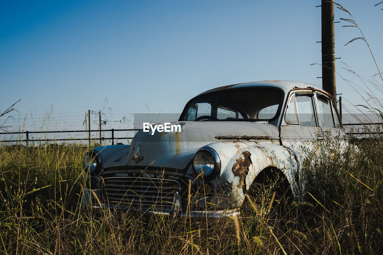 VIEW OF ABANDONED CAR ON LANDSCAPE