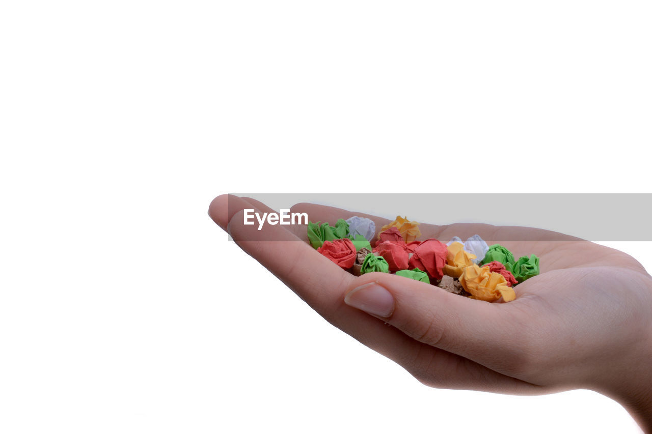 human hand, hand, human body part, white background, studio shot, one person, holding, copy space, body part, food and drink, food, close-up, unrecognizable person, indoors, finger, multi colored, human finger, freshness, sweet food, temptation, snack