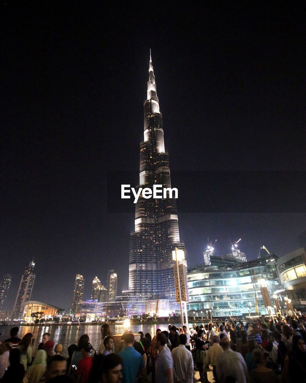 large group of people, illuminated, real people, building exterior, tourism, crowd, architecture, built structure, travel destinations, lifestyles, night, women, leisure activity, travel, men, skyscraper, vacations, modern, outdoors, city, sky, people