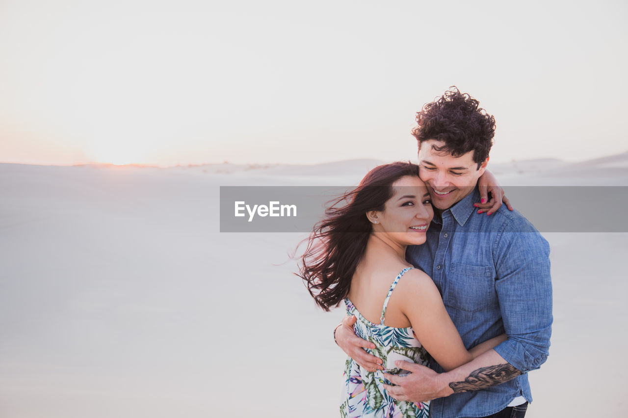 Portrait of smiling girlfriend embracing boyfriend at desert