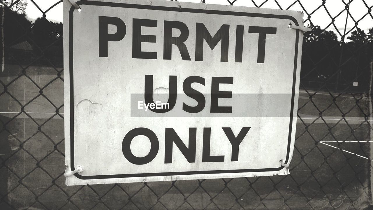 Close-Up Of Text On Chainlink Fence