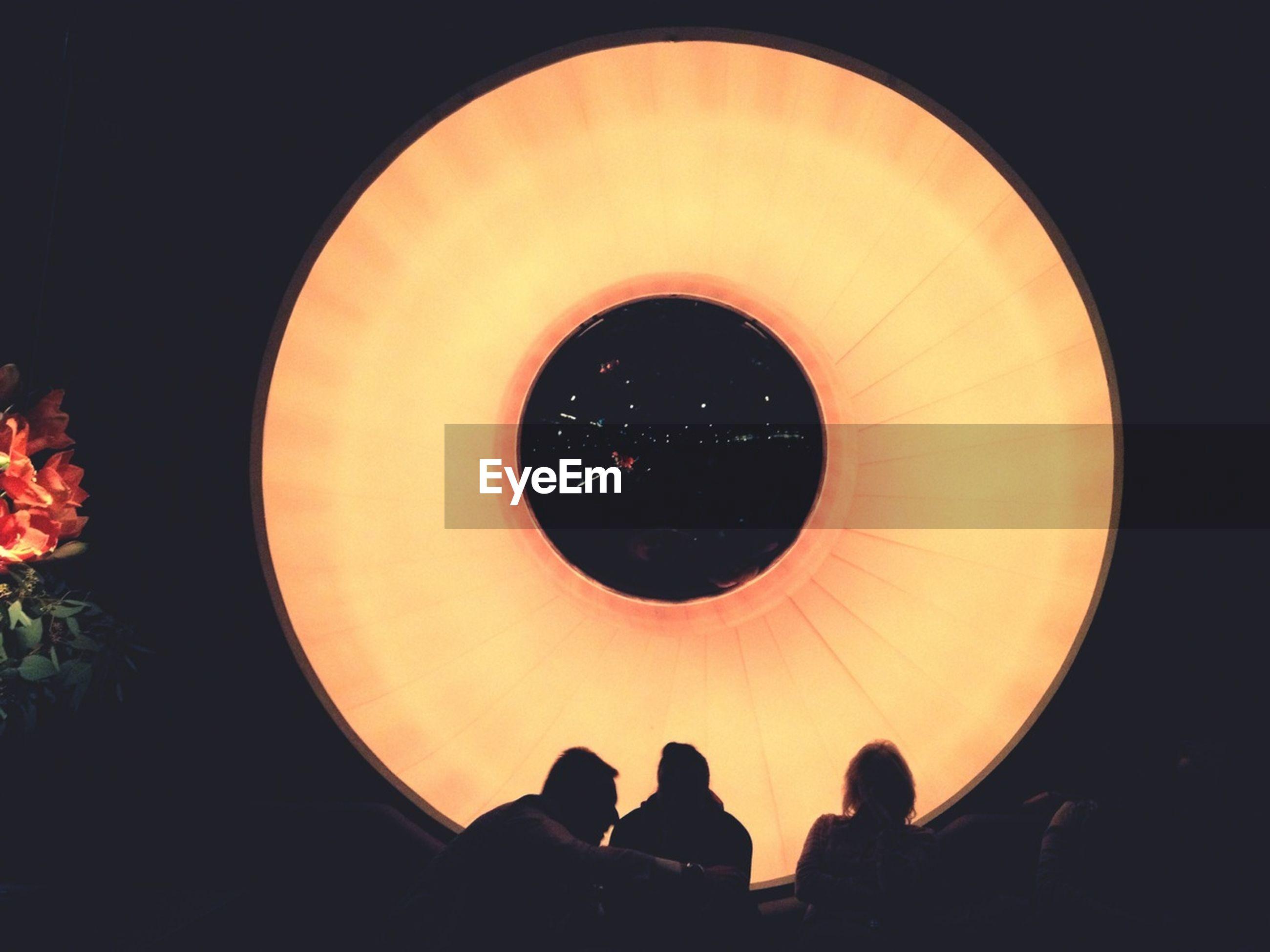 People sitting against illuminated light on wall at restaurant