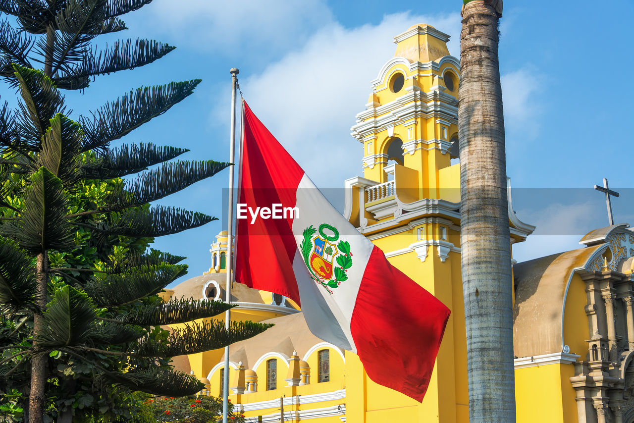 Low angle view of peruvian flag against yellow historic building against sky