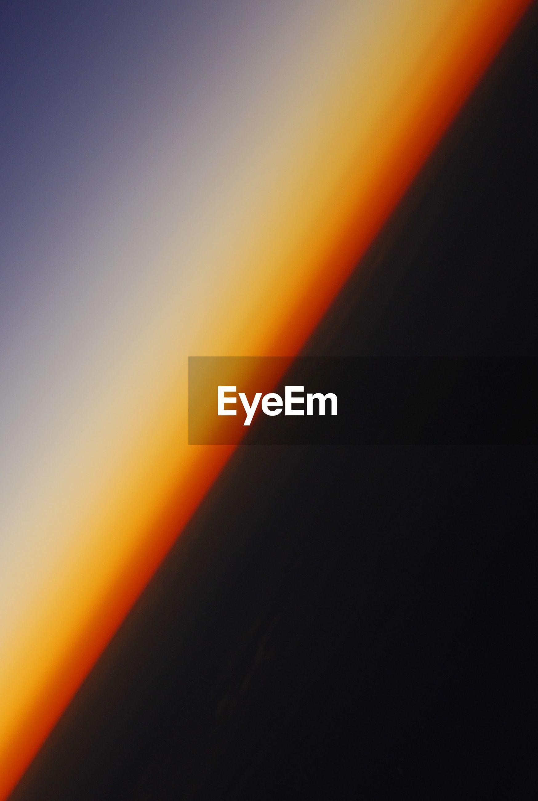 Tilt image of ocean against clear sky during sunset