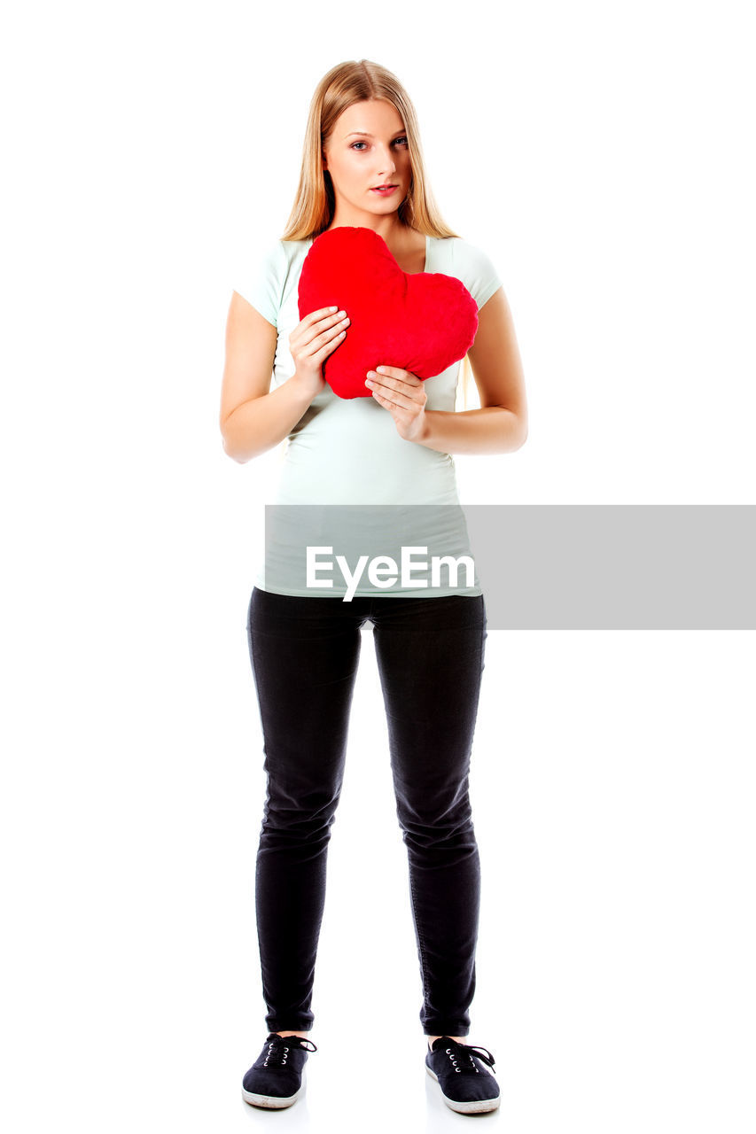 Portrait of young woman holding red heart shape against white background