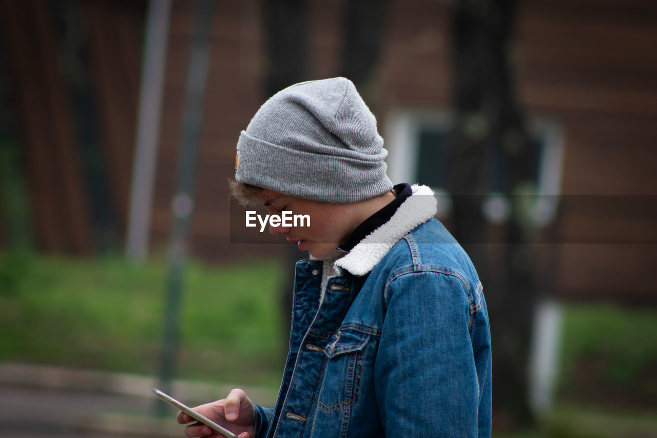 focus on foreground, real people, casual clothing, one person, lifestyles, leisure activity, side view, wireless technology, clothing, standing, child, communication, day, denim, connection, mobile phone, childhood, technology, outdoors, jeans, profile view, warm clothing, innocence