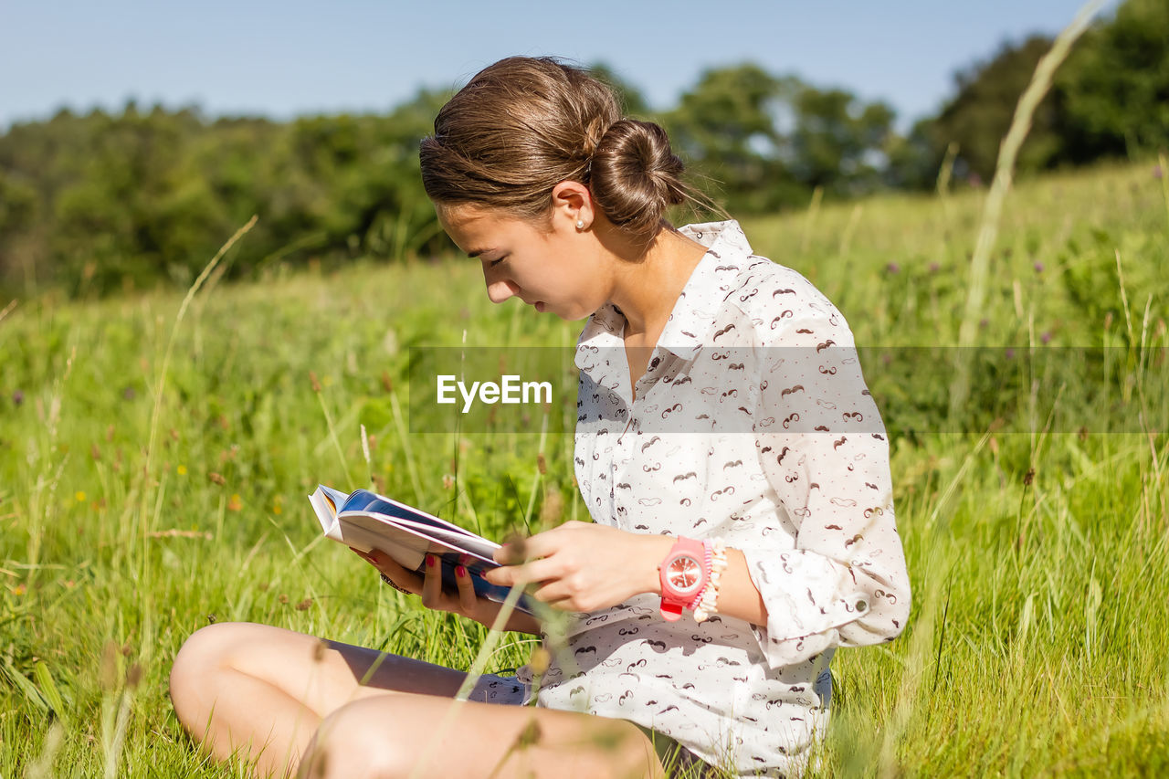 YOUNG WOMAN USING SMART PHONE IN FIELD