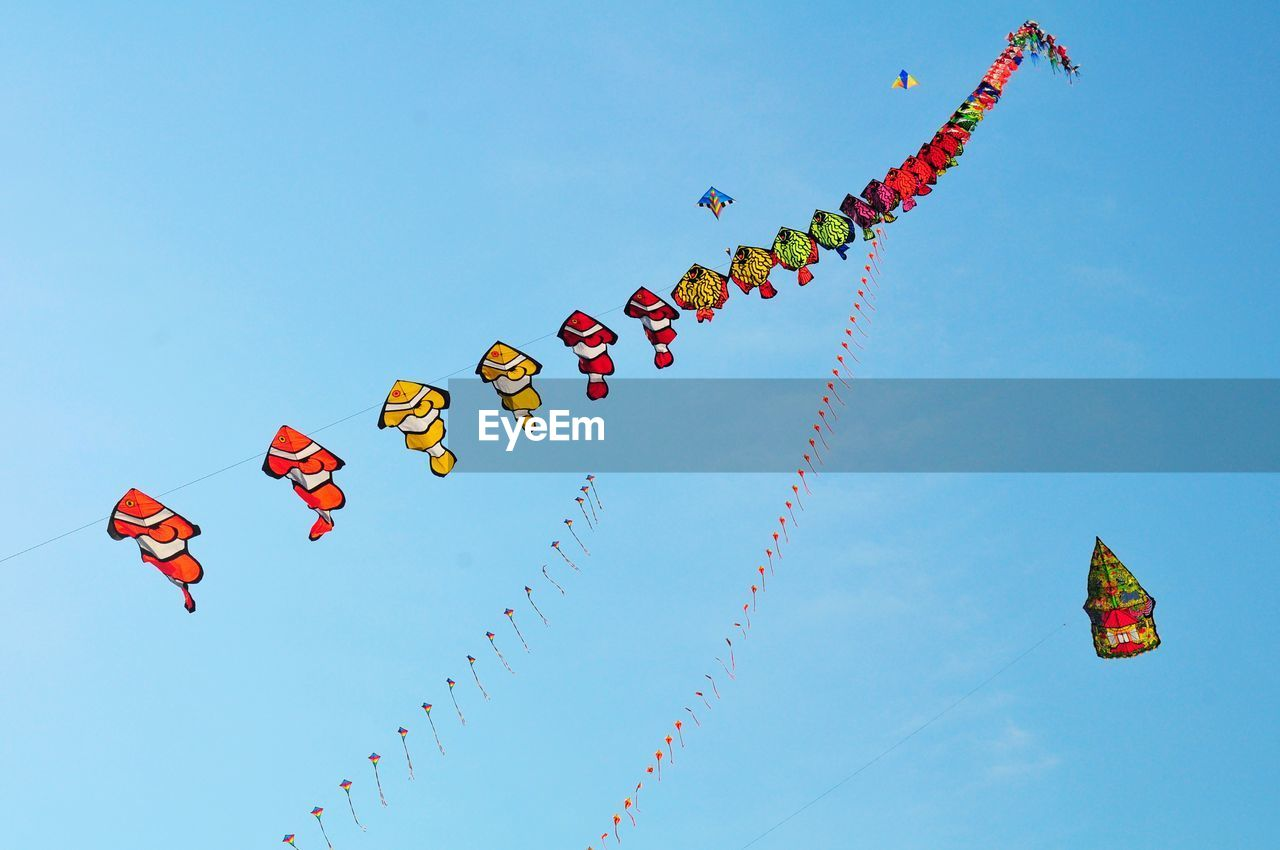 multi colored, sky, low angle view, nature, decoration, no people, celebration, hanging, blue, day, kite - toy, art and craft, creativity, flag, clear sky, flying, shape, in a row, large group of objects, wind