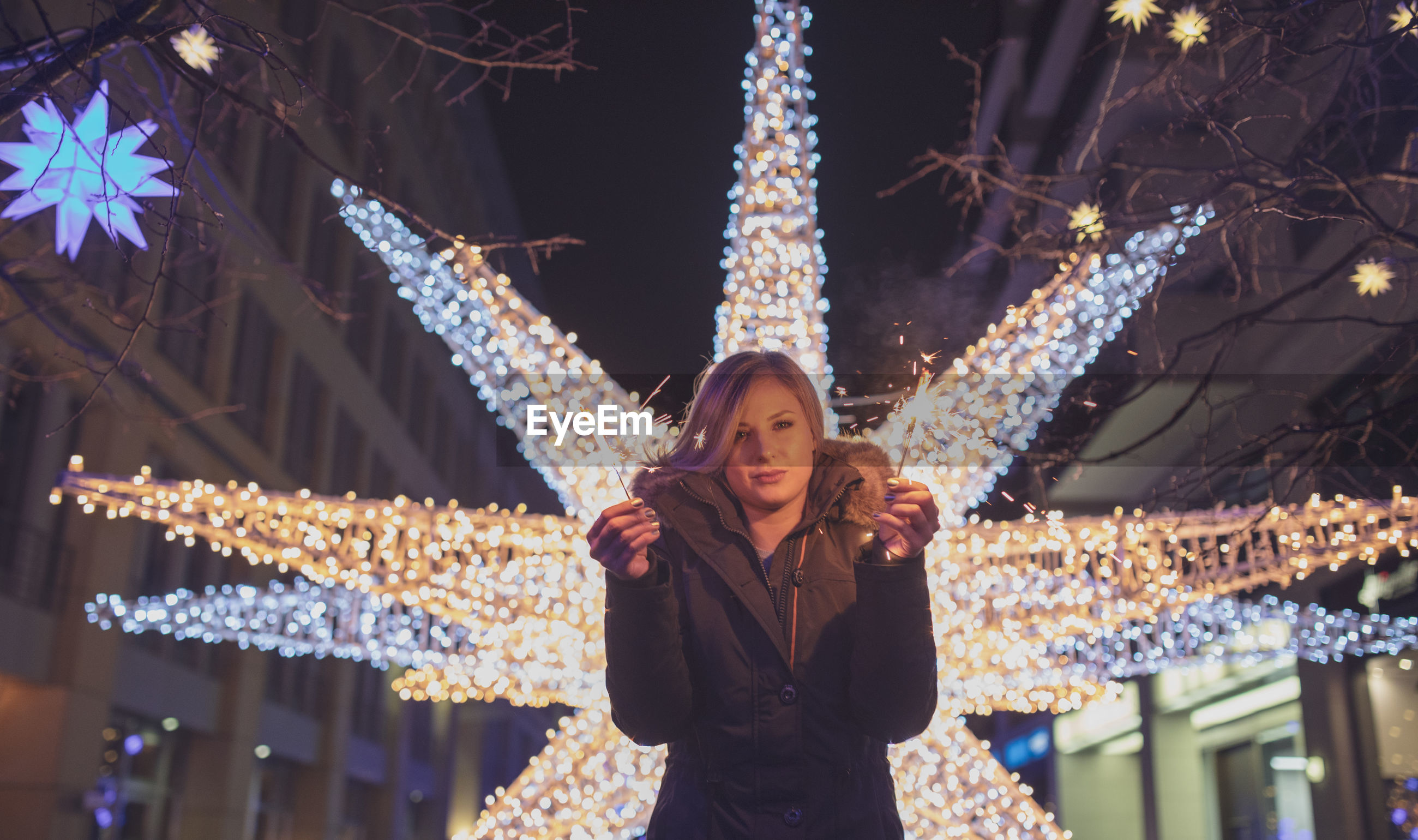 Portrait of woman holding illuminated sparkler at night