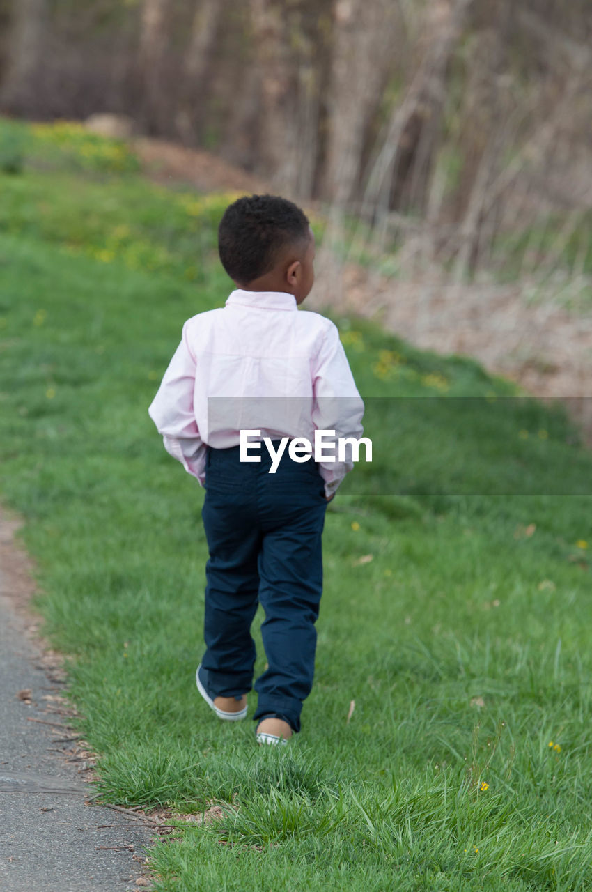 real people, full length, childhood, one person, grass, rear view, casual clothing, field, walking, boys, green color, nature, leisure activity, outdoors, lifestyles, day, standing, growth, tree, people