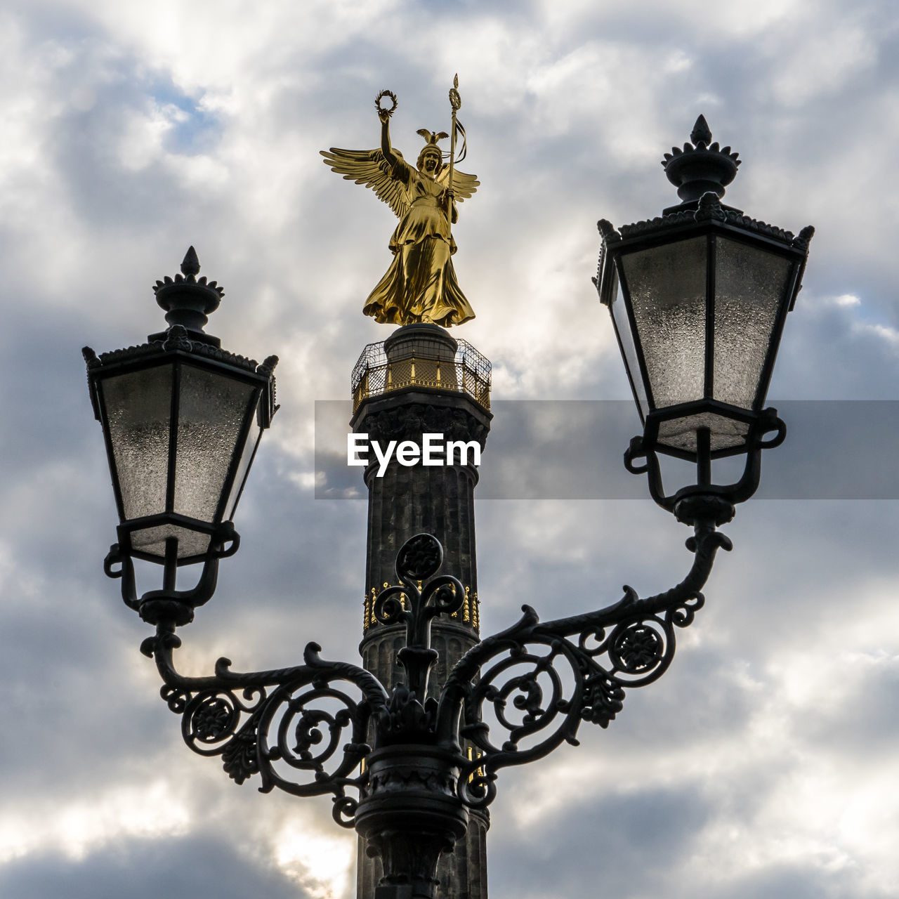 cloud - sky, street light, sky, lighting equipment, street, low angle view, no people, art and craft, sculpture, nature, architecture, representation, gold colored, human representation, travel destinations, statue, history, the past, outdoors, day, ornate, antique, electric lamp