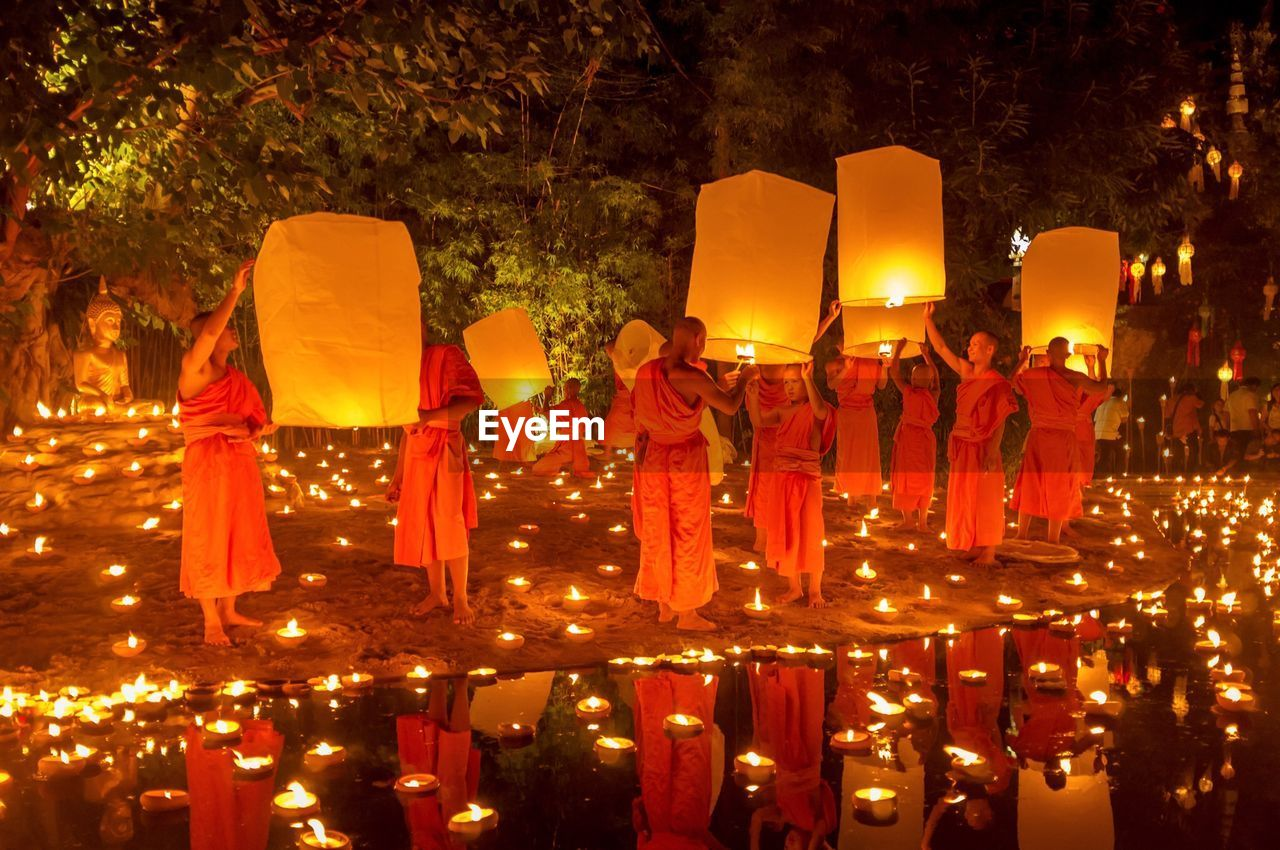 tree, celebration, illuminated, night, men, real people, outdoors, lantern, rear view, red, large group of people, togetherness, people