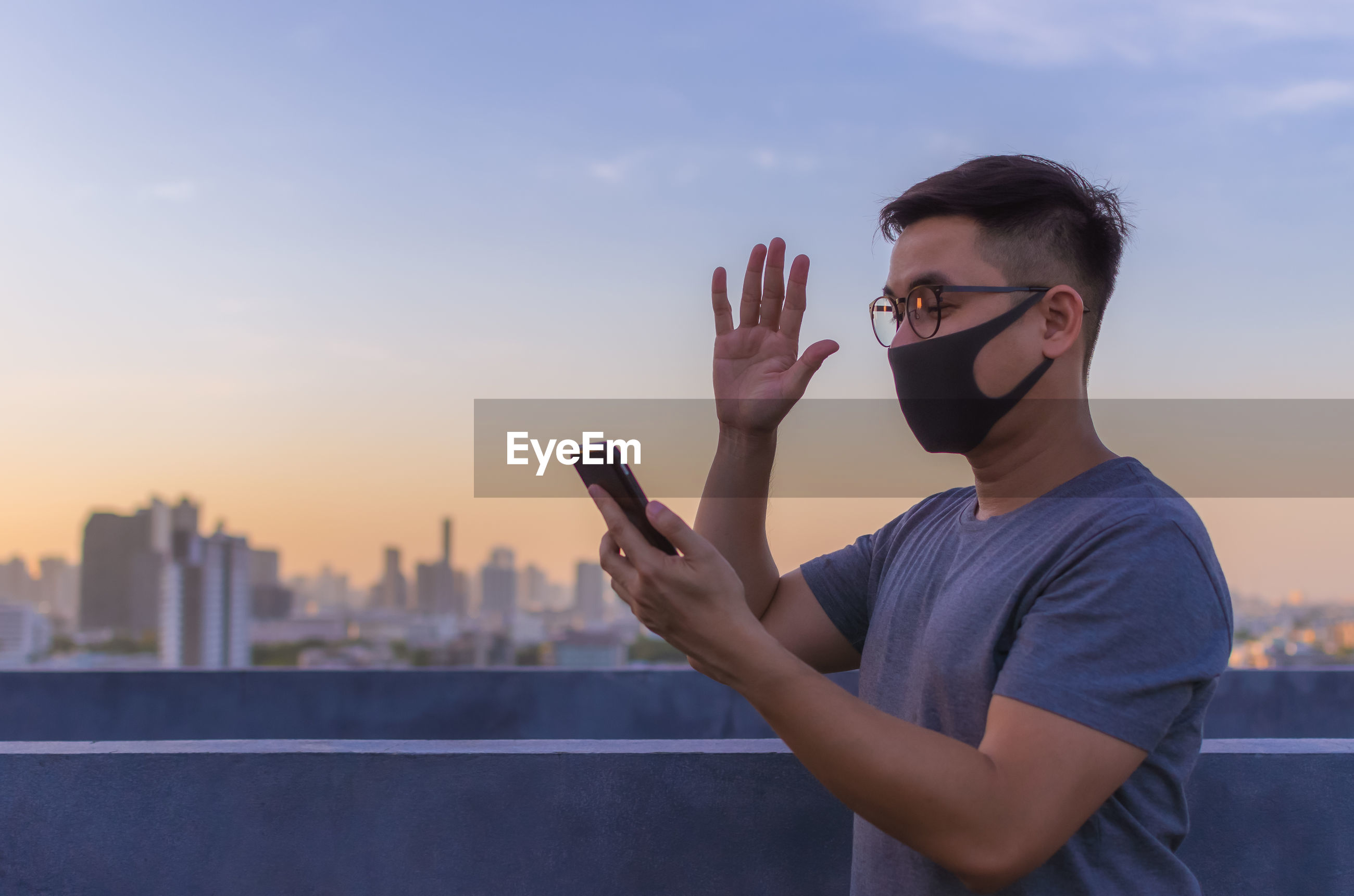 Asian man wearing face mask to protect from virus and make a video call with smartphone.